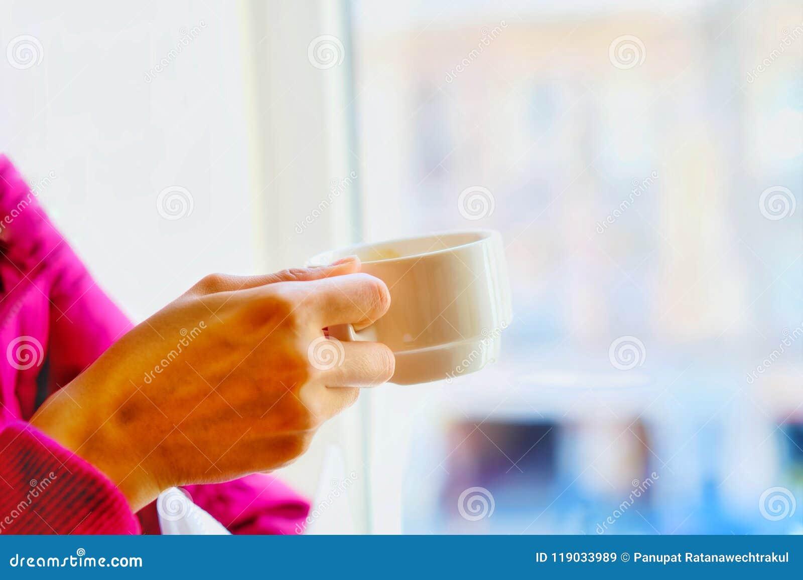手有一杯咖啡的妇女在白色颜色的