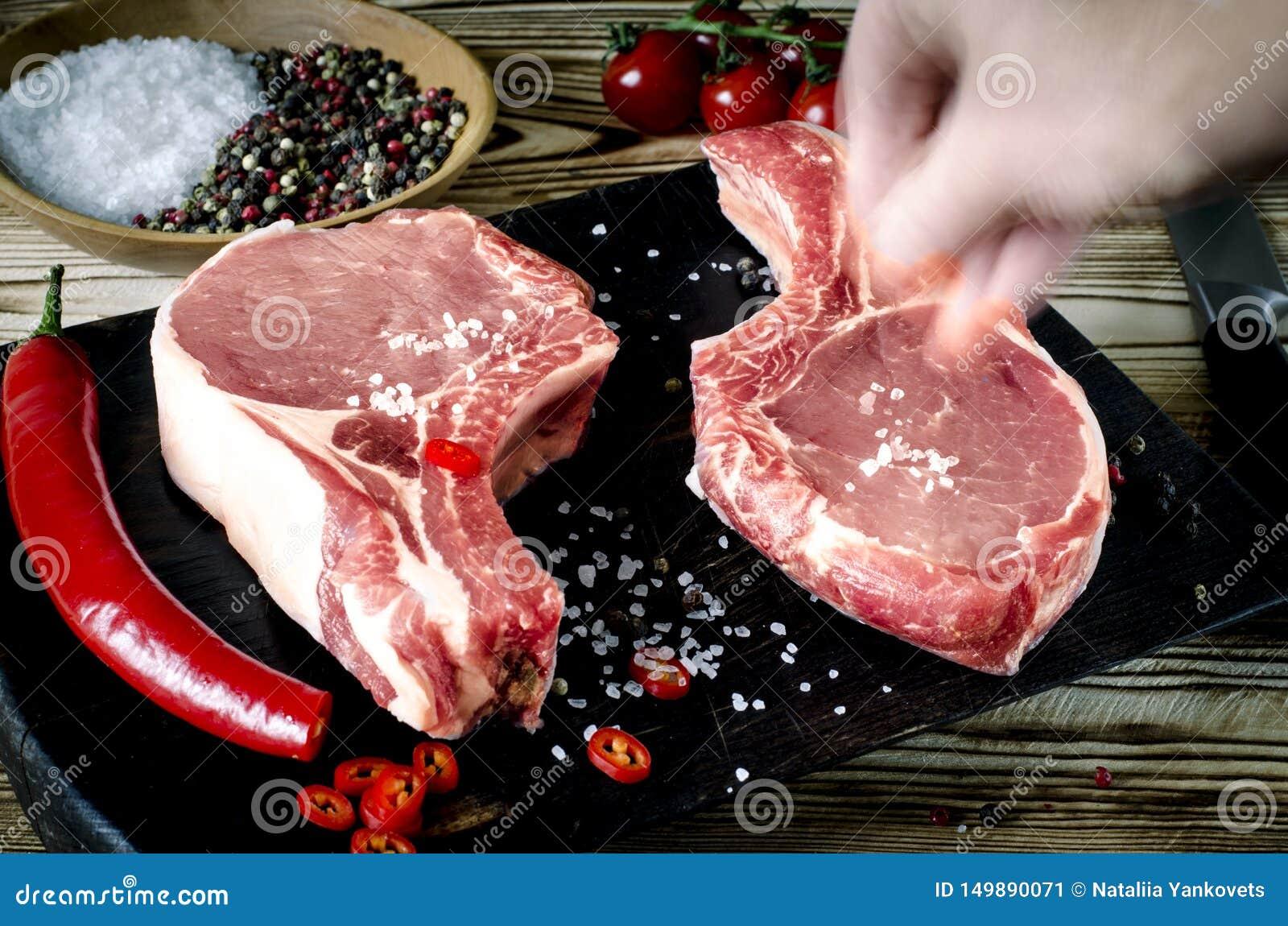 手盐肉牛排 未加工的使有大理石花纹的肉牛排,胡椒,草本,大蒜,老木背景 r 牛肋骨眼睛牛排