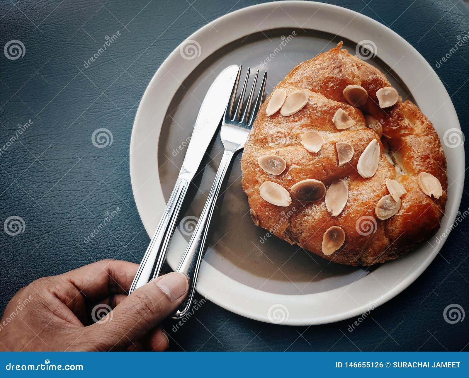手采摘刀子和叉子吃新月形面包用在上面的切的杏仁