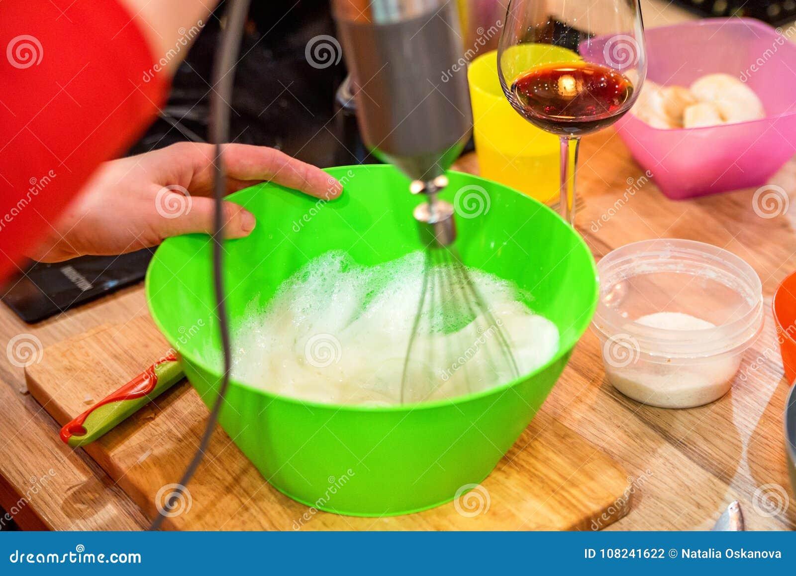 手鞭打在塑料碗关闭的鸡蛋