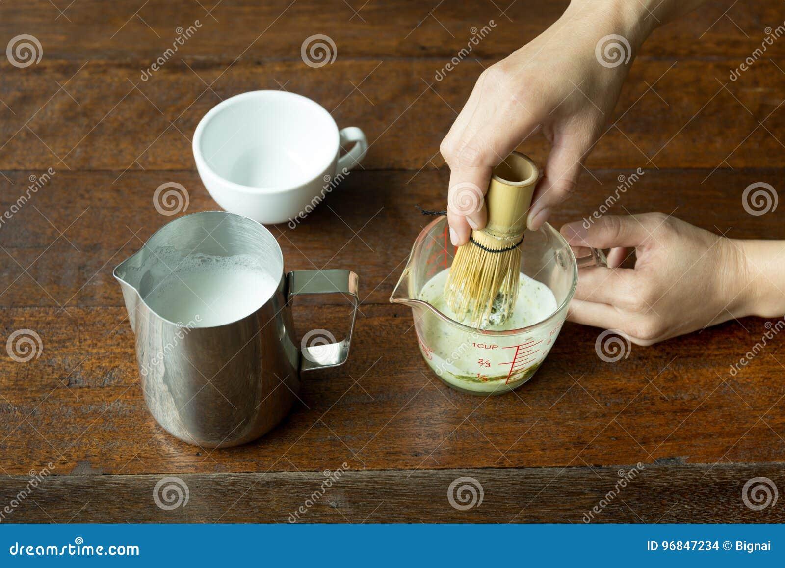 手活泼的matcha绿茶用茶在玻璃瓶子扫与