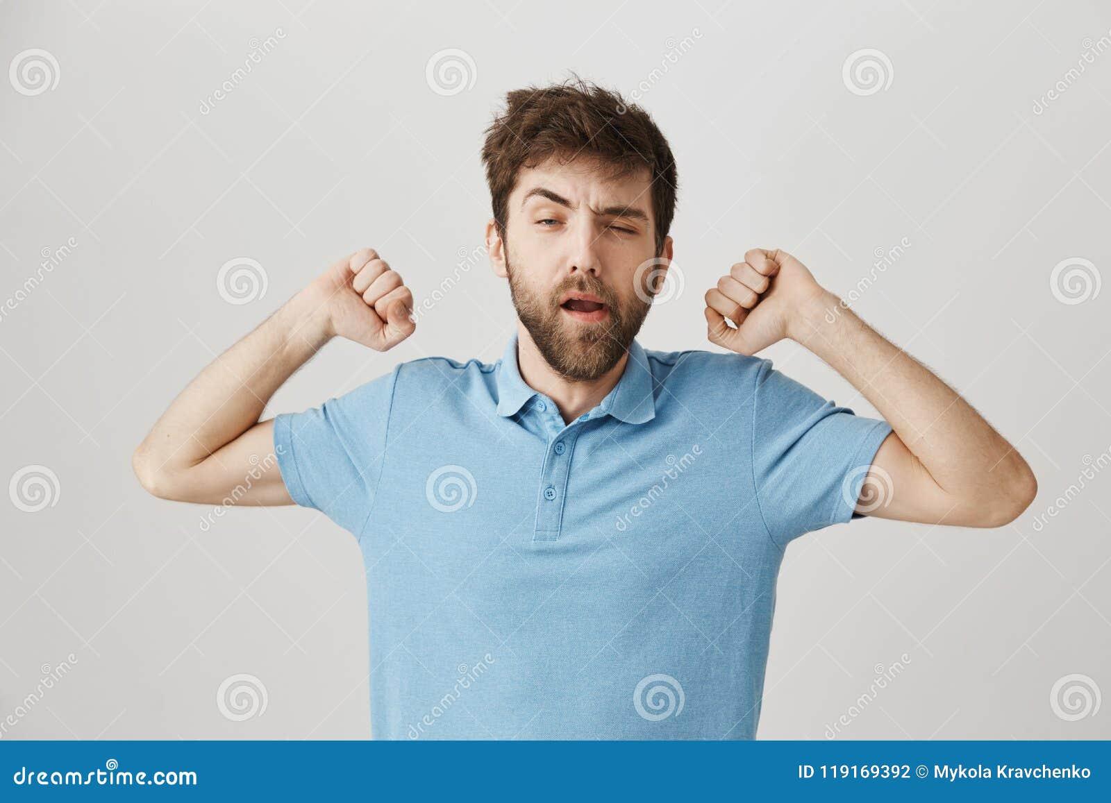打呵欠杂乱和困成人有胡子的人舒展用被举的手和,斜眼看,好象他醒了,站立