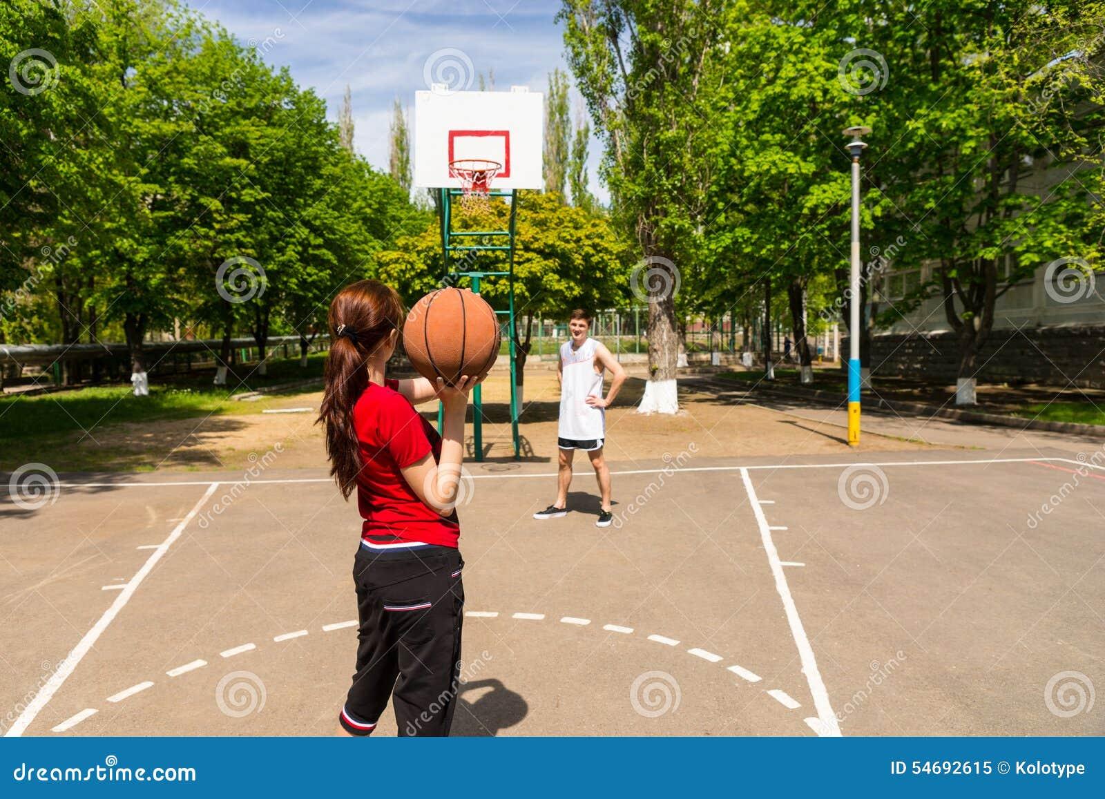 打在室外法院的夫妇篮球