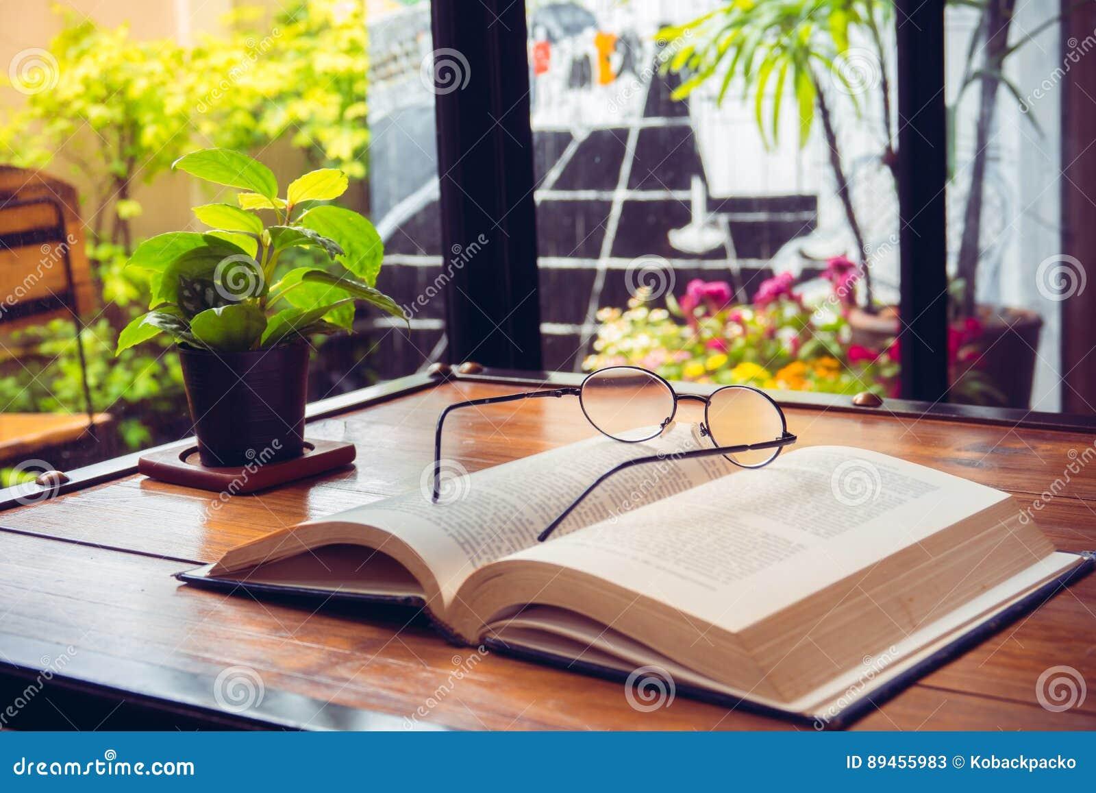 打开与玻璃的旧书在咖啡馆的木桌上