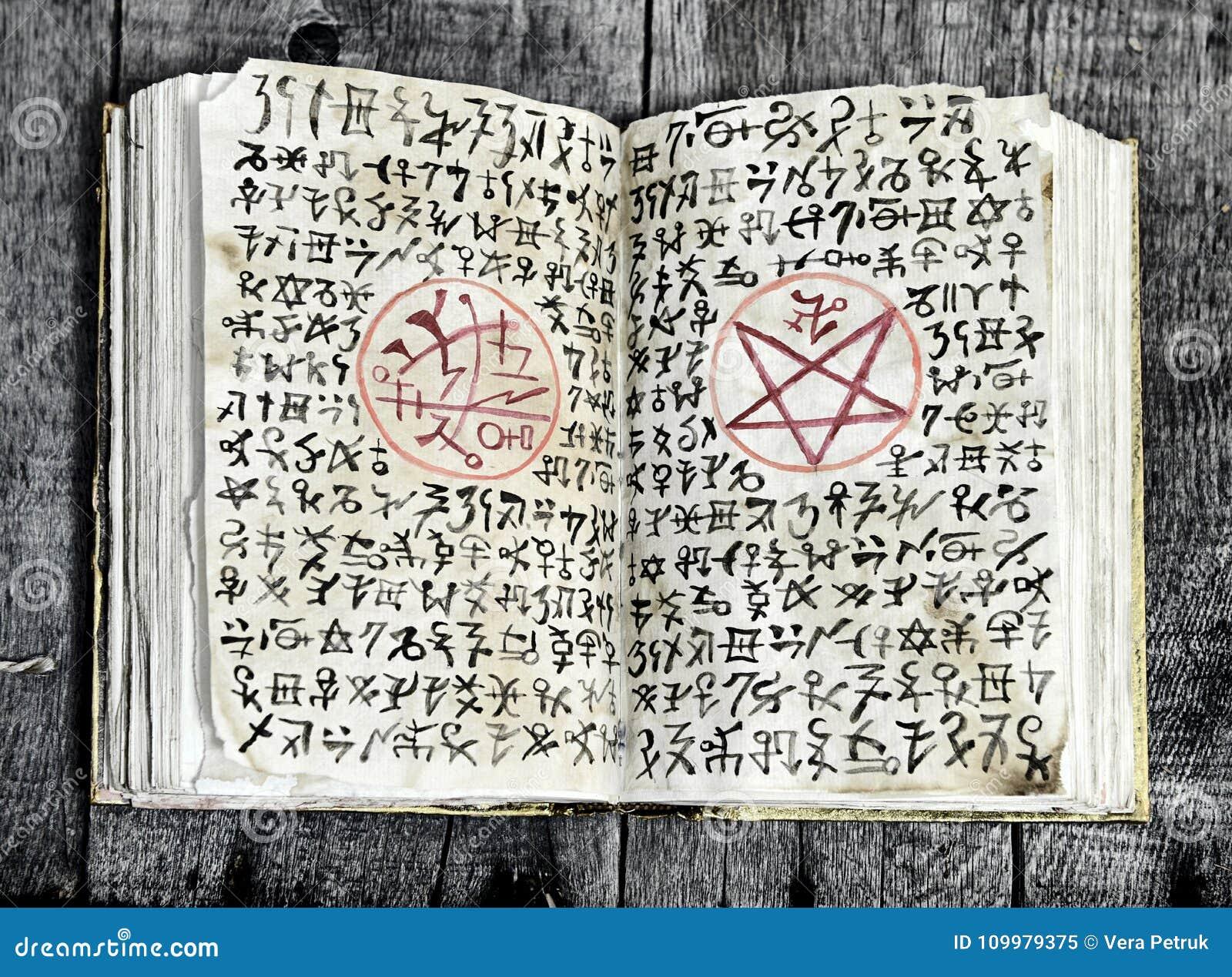 打开与邪恶的标志和五角星形的不可思议书在破旧的页