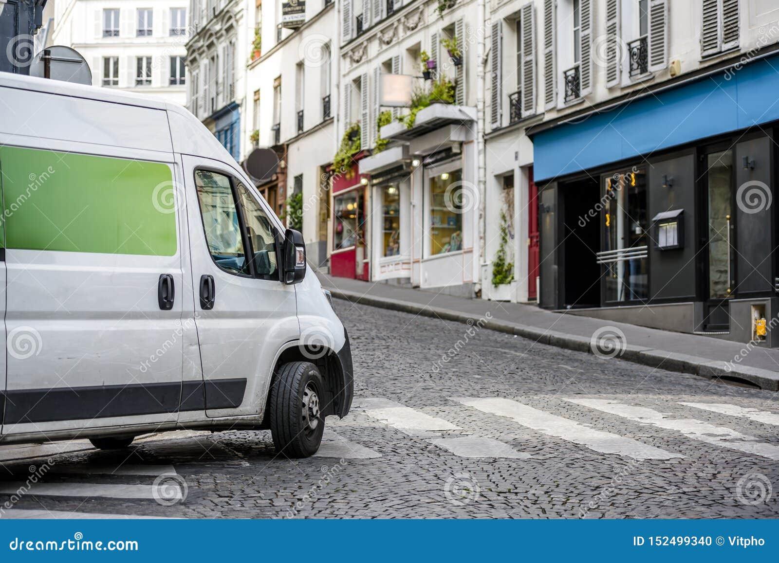 打开在城市街道上的小企业和地方交付的紧凑经济微型搬运车交叉路
