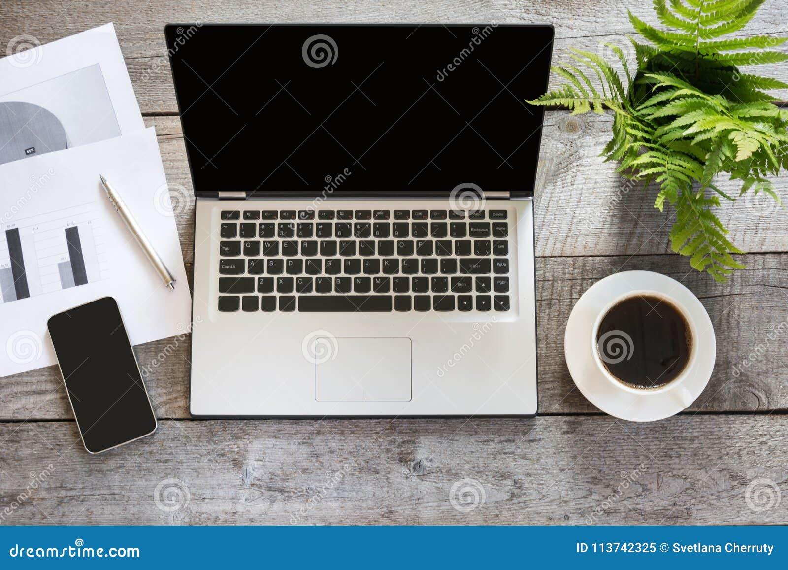 打开有文献的膝上型计算机在办公室木书桌桌上 顶视图