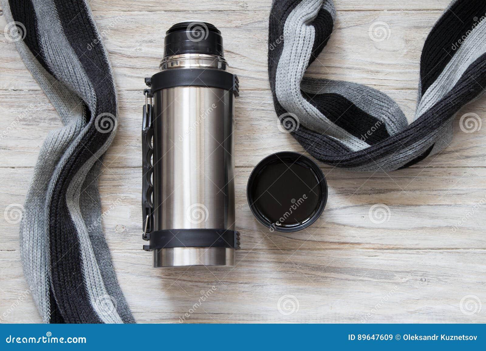 打开热水瓶烧瓶和围巾在woden背景 顶视图