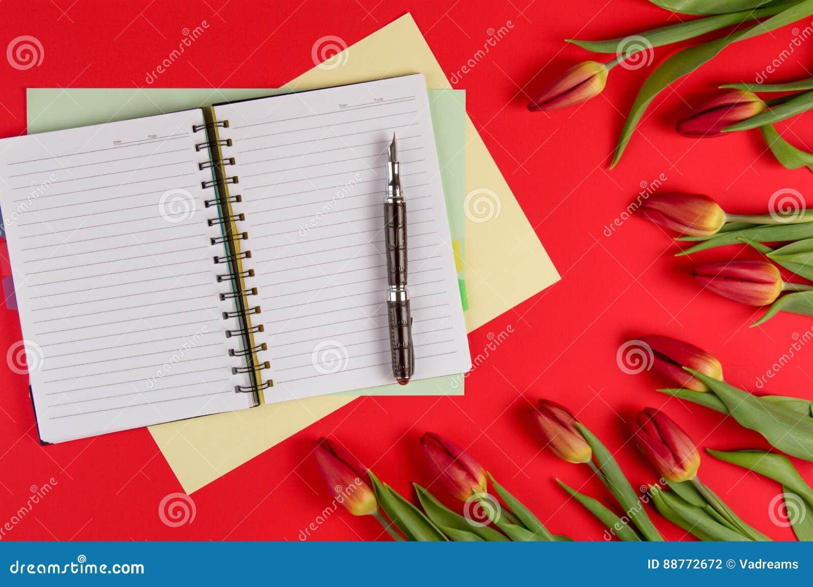 打开纸笔记本,纸牌和笔在红色背景与美好的新花郁金香
