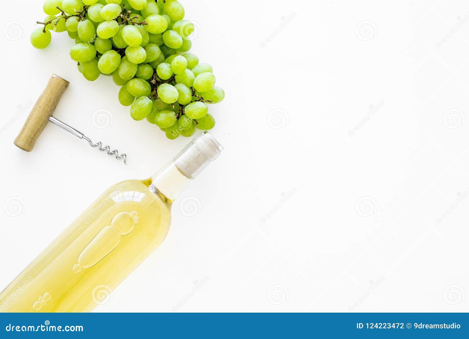 打开酒概念 在玻璃瓶的在白色背景顶视图的白葡萄酒在葡萄附近和拔塞螺旋复制