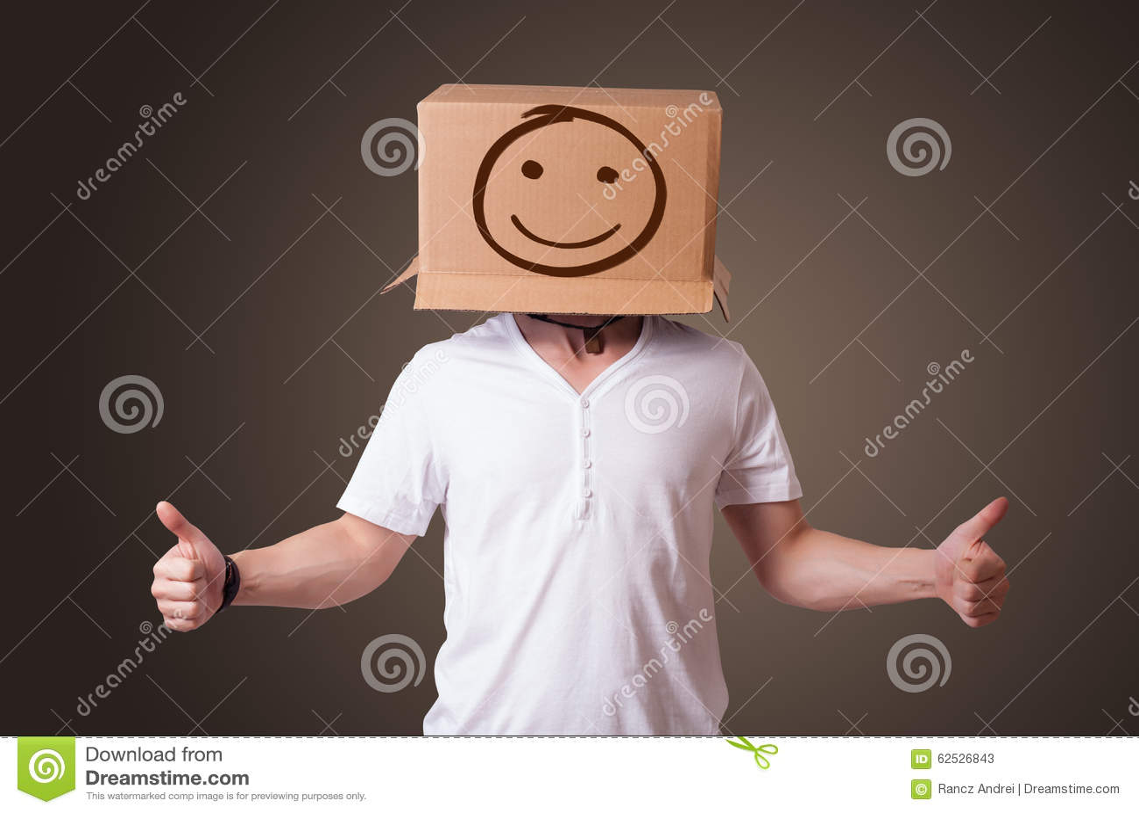 打手势与在他的头的一个纸板箱的年轻人有面带笑容的
