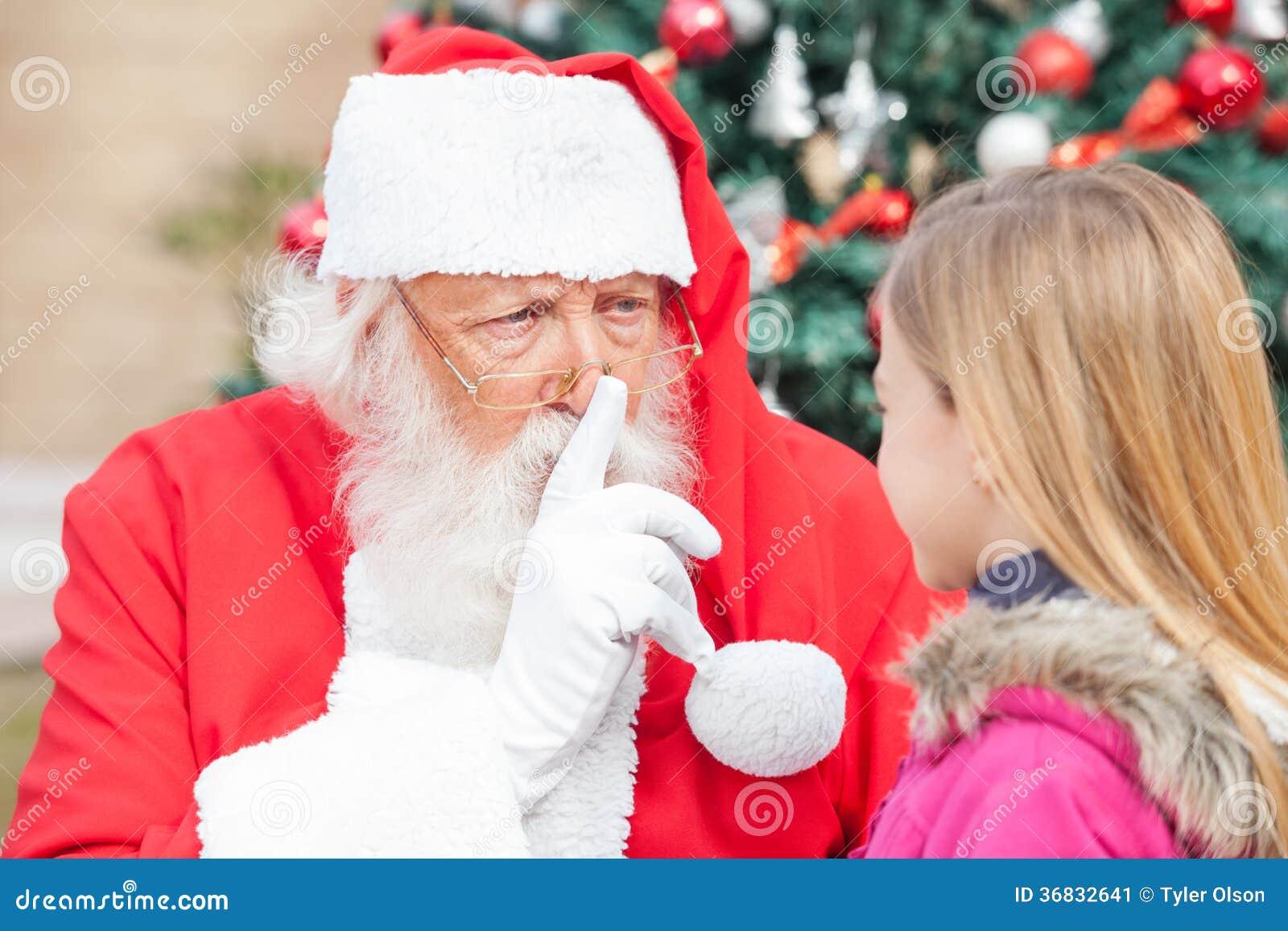 打手势在嘴唇的圣诞老人手指,当看时