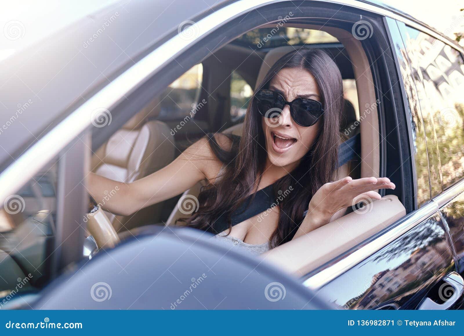 打手势的妇女,当驾驶汽车时