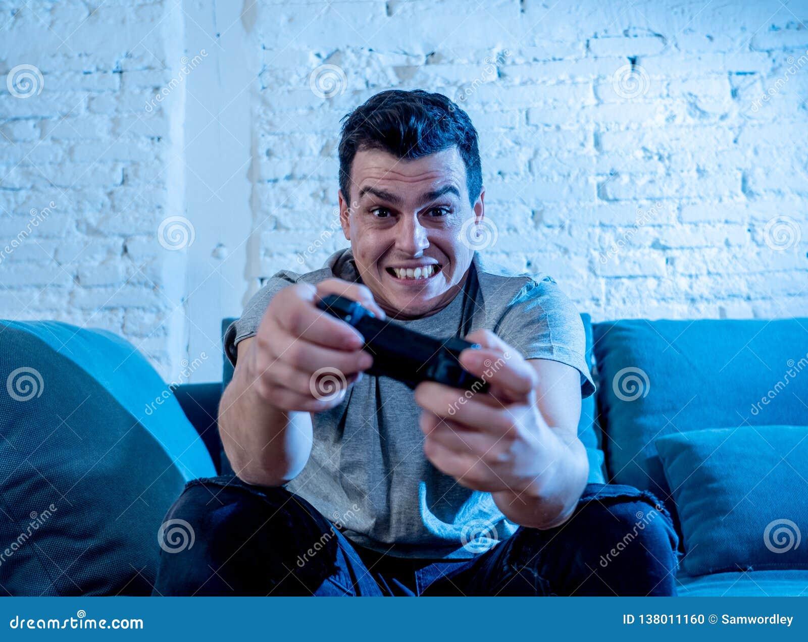打电子游戏的年轻人接近的画象在晚上使上瘾对它获得乐趣