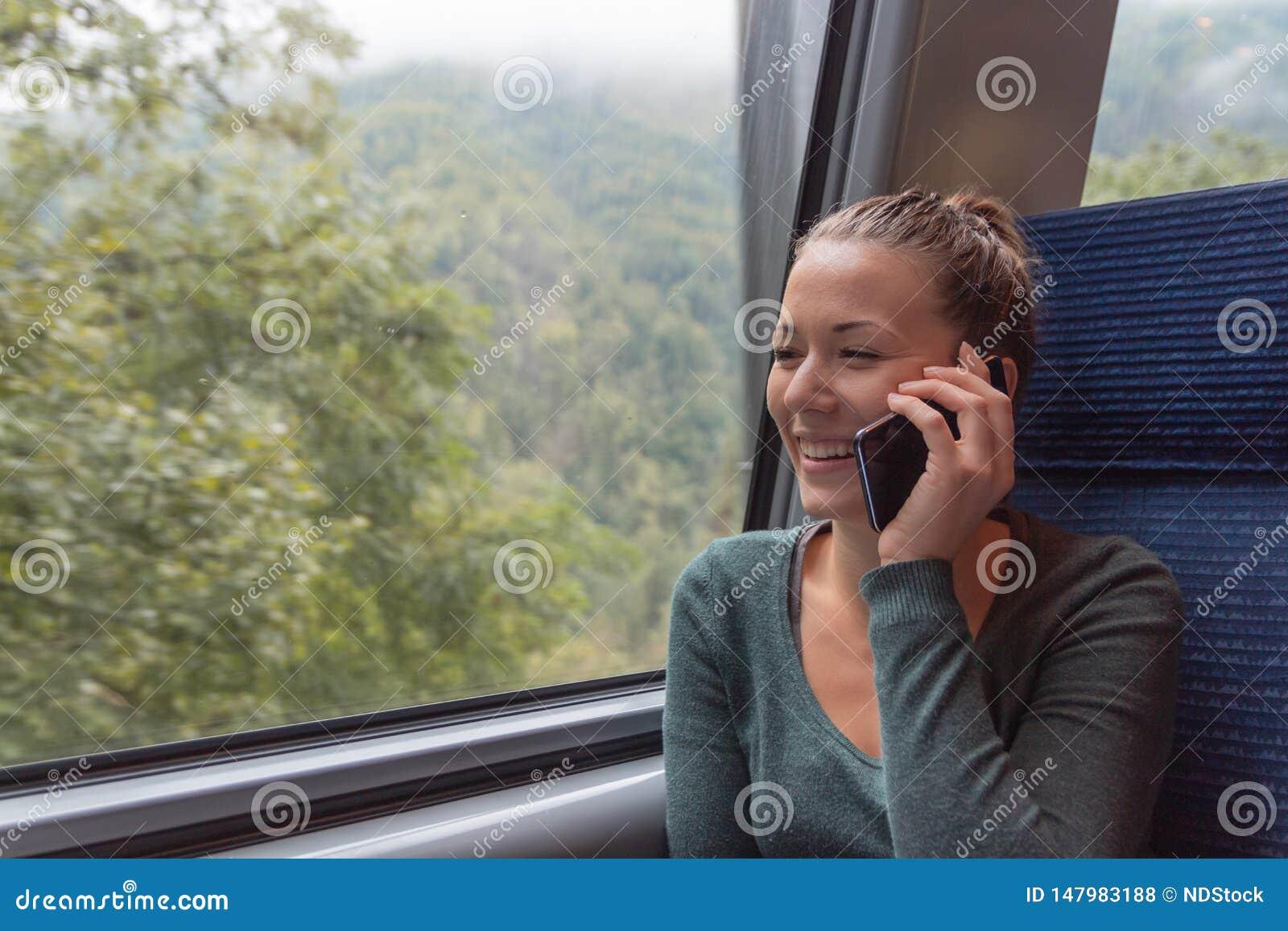 打电话与他的智能手机的年轻女人在火车的一次旅途期间,当她工作时