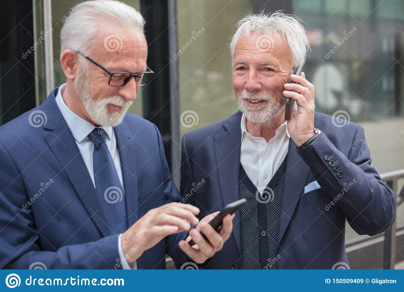 打电话的两个愉快的资深商人,站立在边路