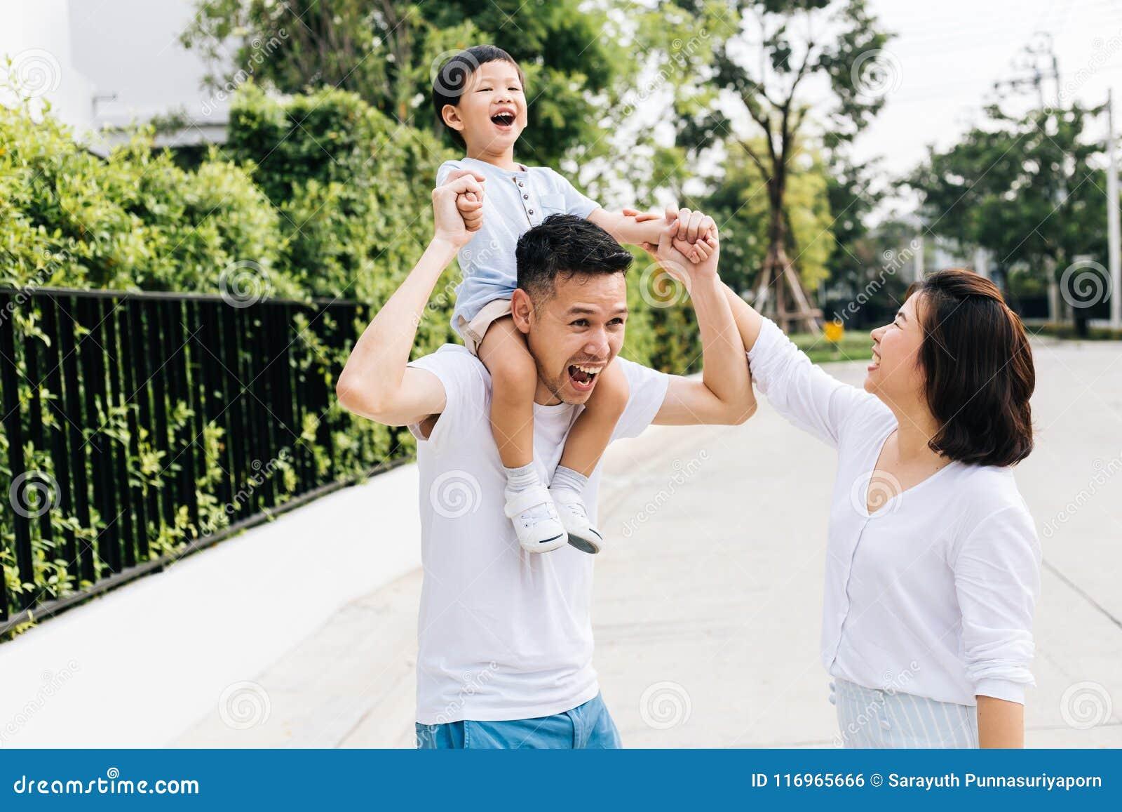 扛在肩上他的儿子的逗人喜爱的亚裔父亲与他的妻子一起在公园 举手的激动的家庭与幸福一起