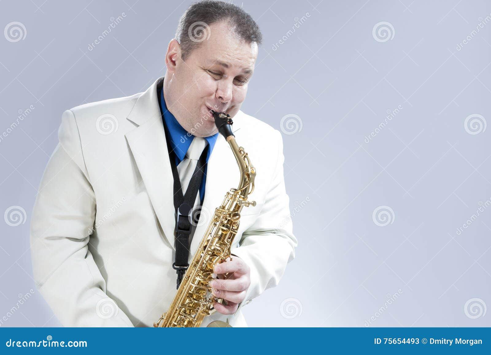 执行在白色衣服的传神男性萨克斯管音乐家自然画象
