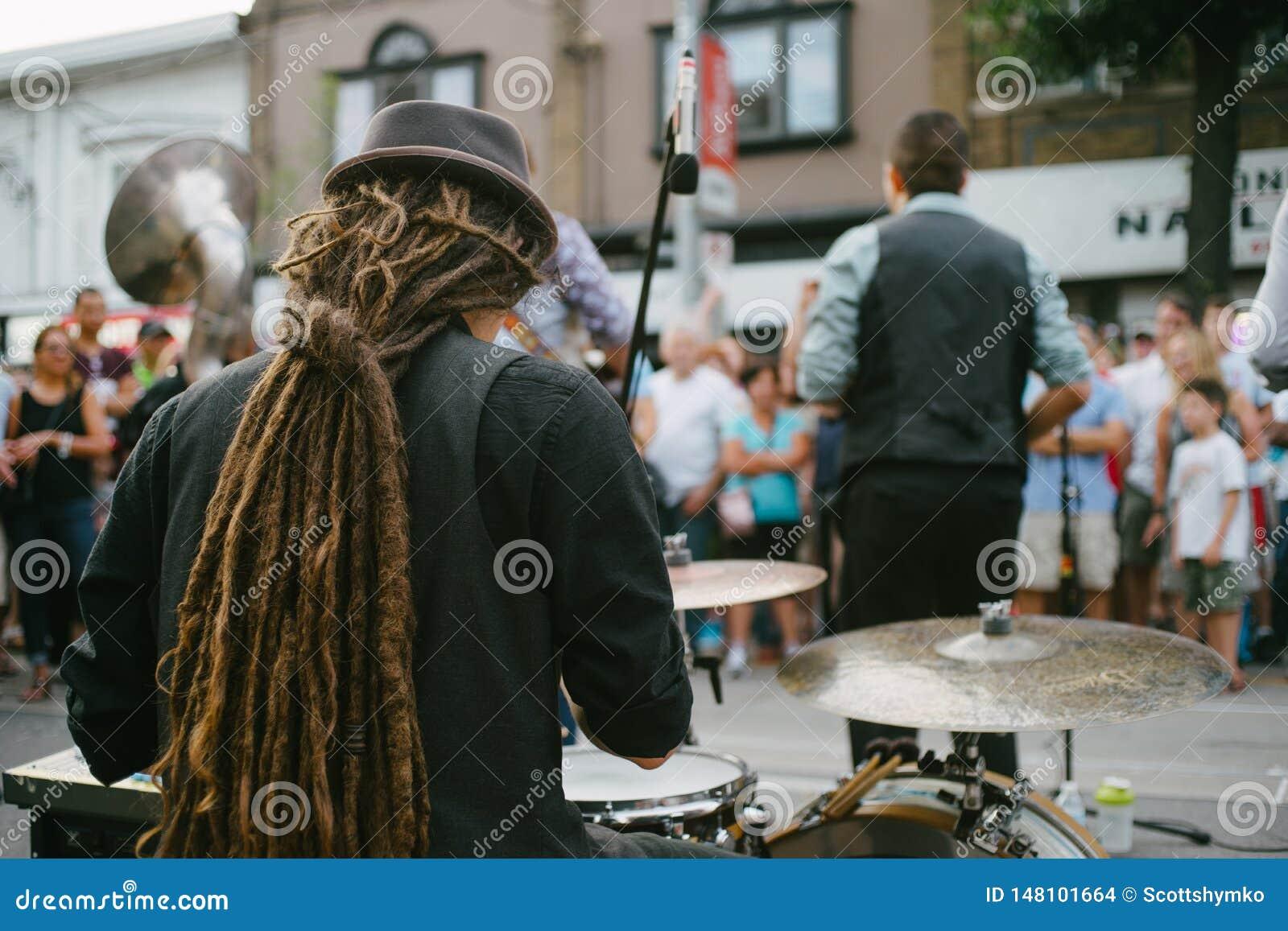 执行在街道上的鼓手和带实况音乐