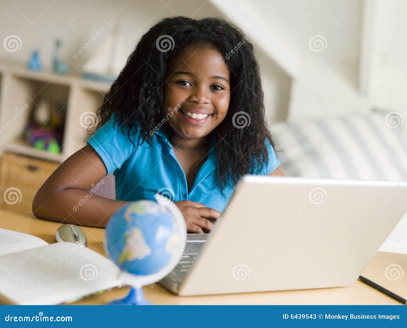 执行女孩她的家庭作业膝上型计算机年轻人