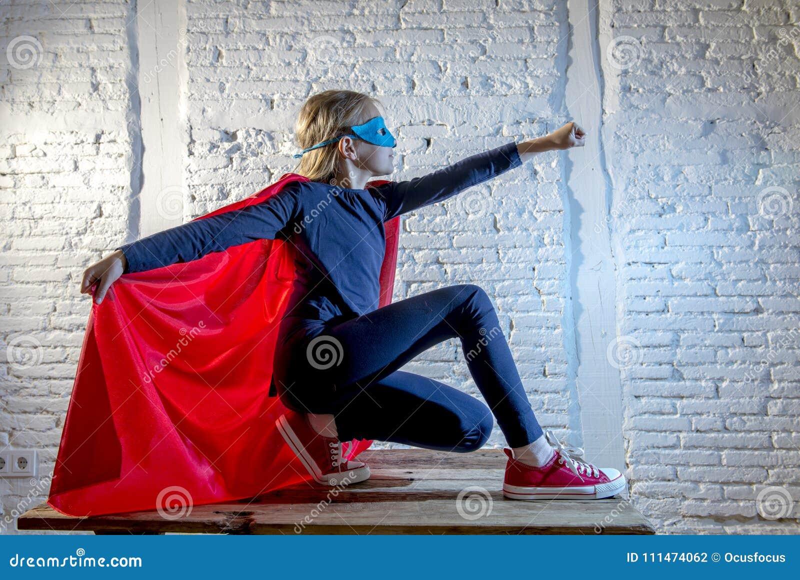 执行愉快和激动的摆在的佩带的盖帽和面具的女孩7或8岁女孩在特级英雄幻想服装lo