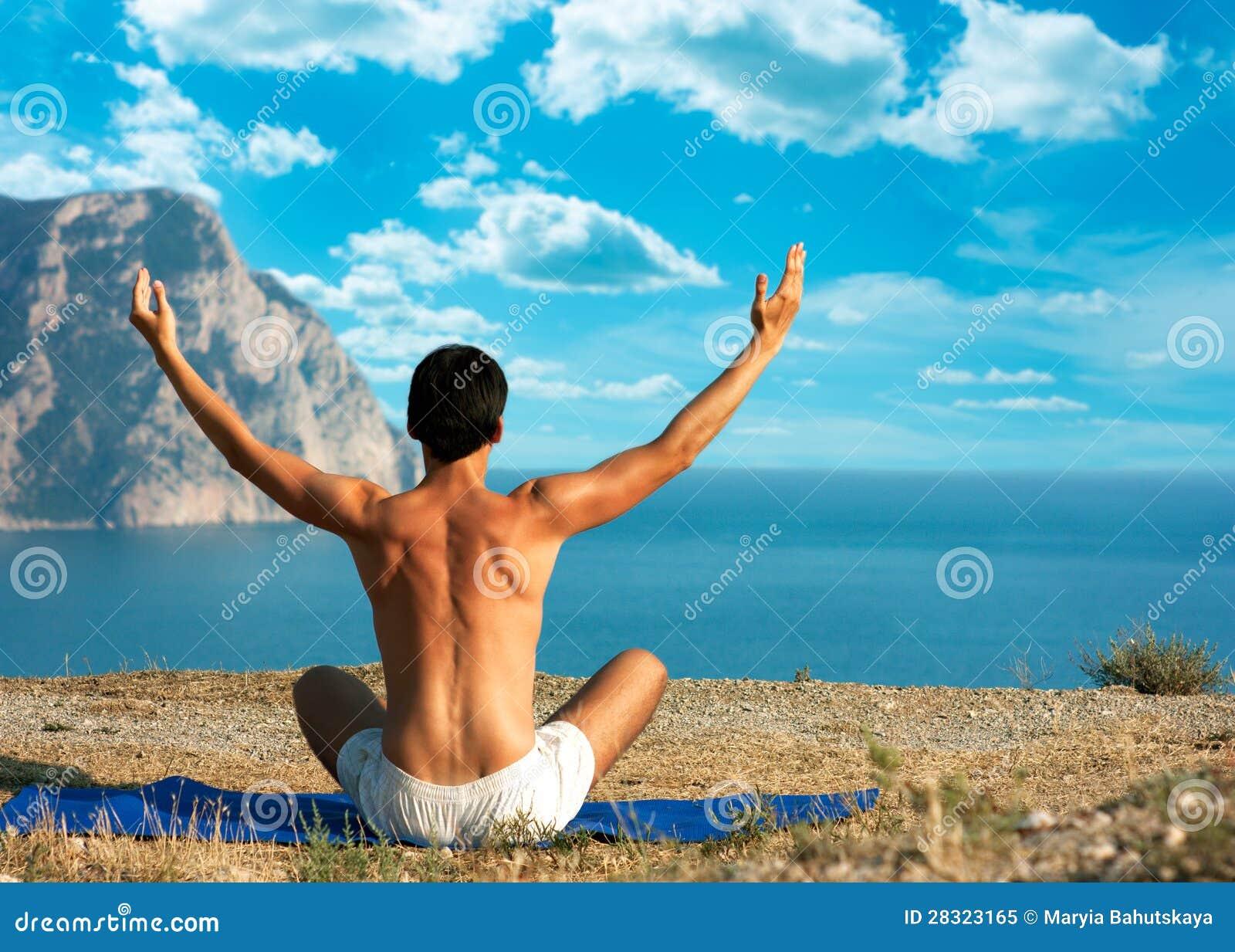 执行瑜伽的人在海运和山