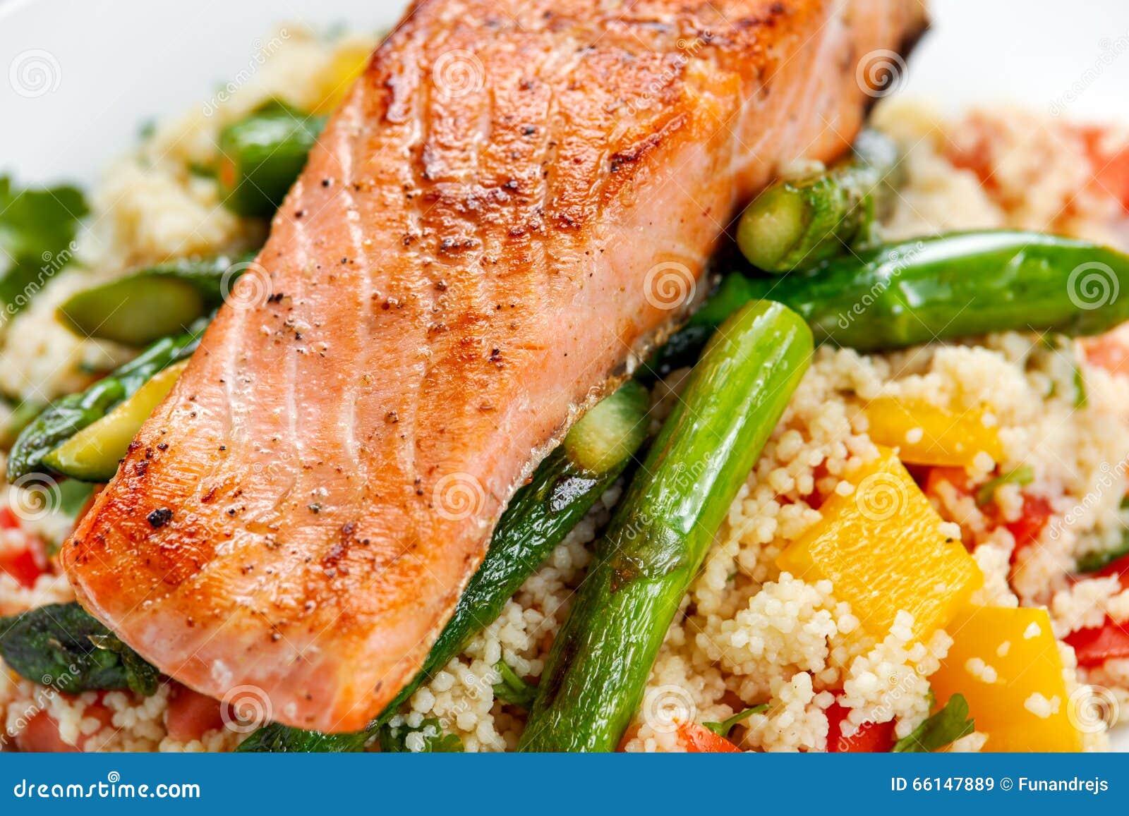 批评油煎的三文鱼用嫩在蒸丸子供食的芦笋和绿皮胡瓜混合与甜蕃茄,黄色胡椒辣调味汁