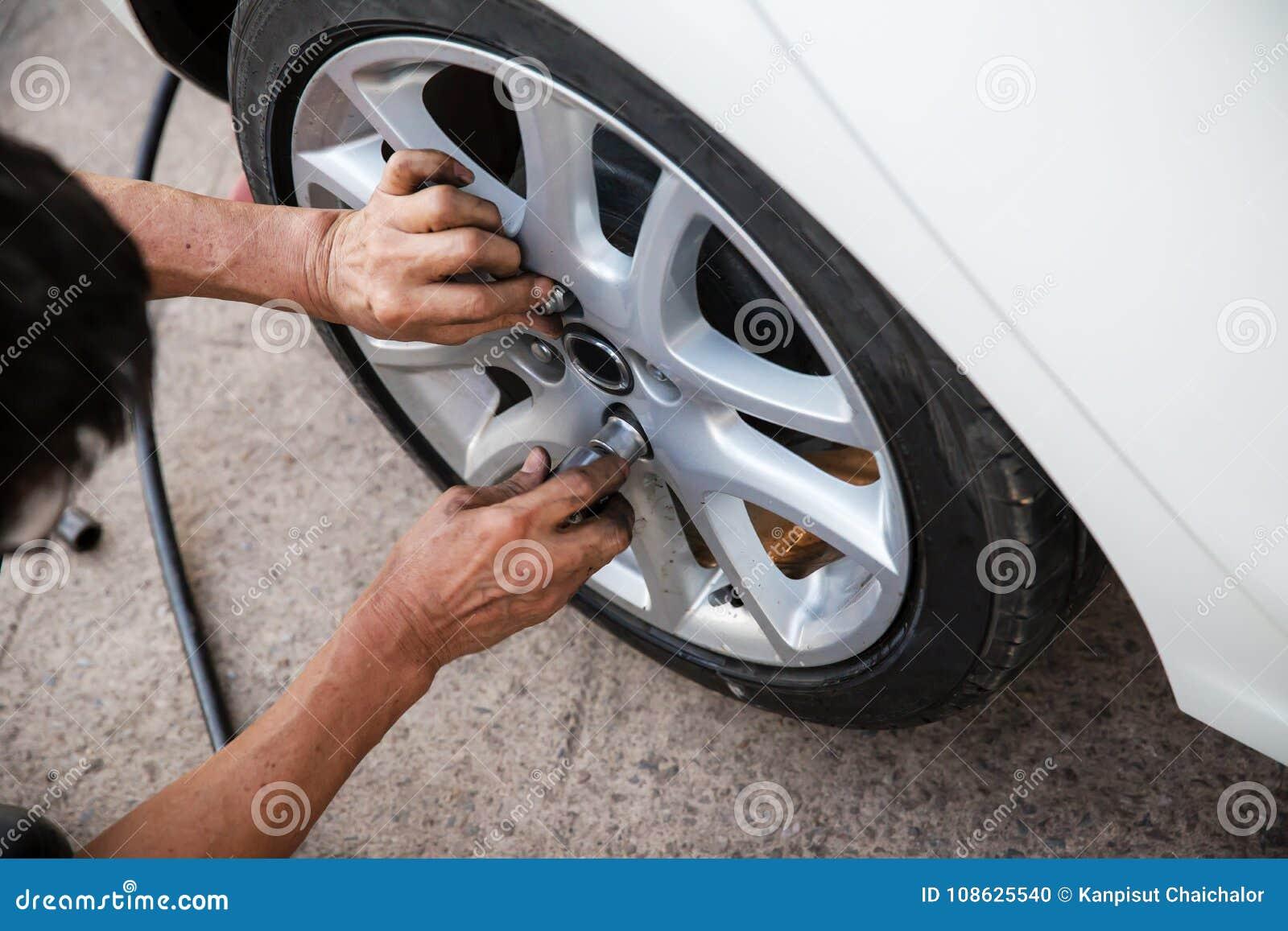 技术员工作者拧紧有一把手工板钳的轮子螺栓 维护和检查汽车概念 的检查和定象veh