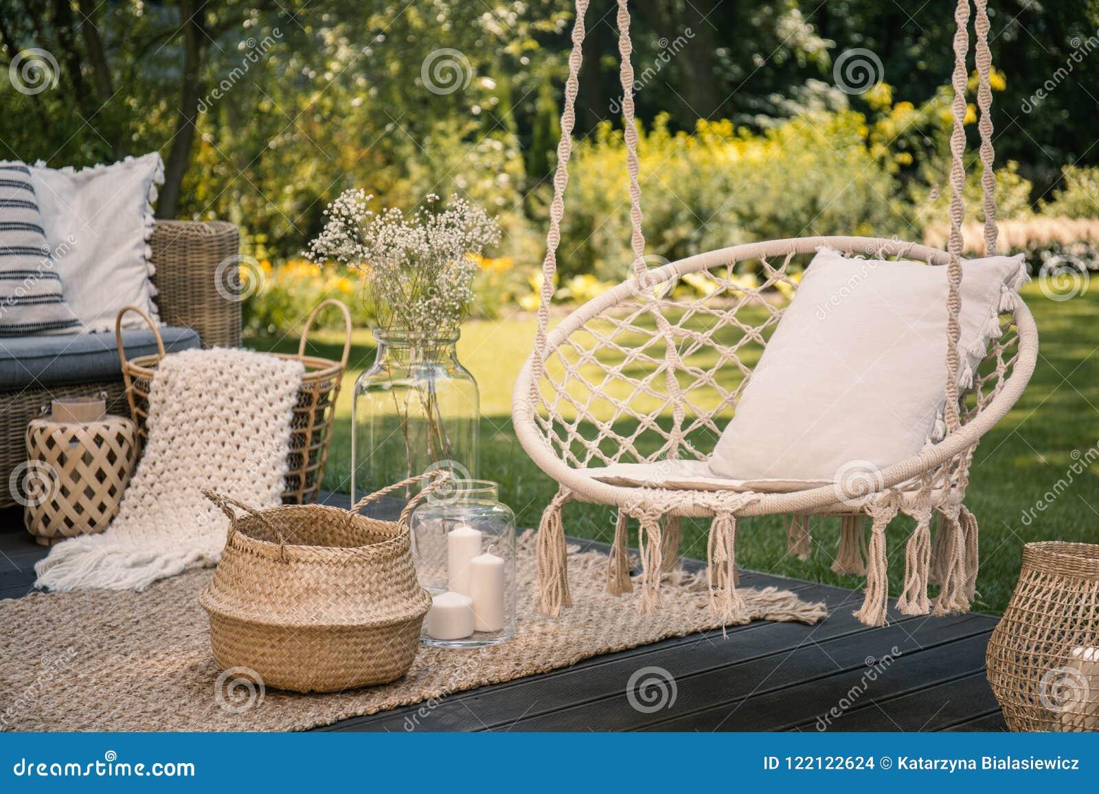 把枕在垂悬的椅子和篮子在地毯在庭院里与