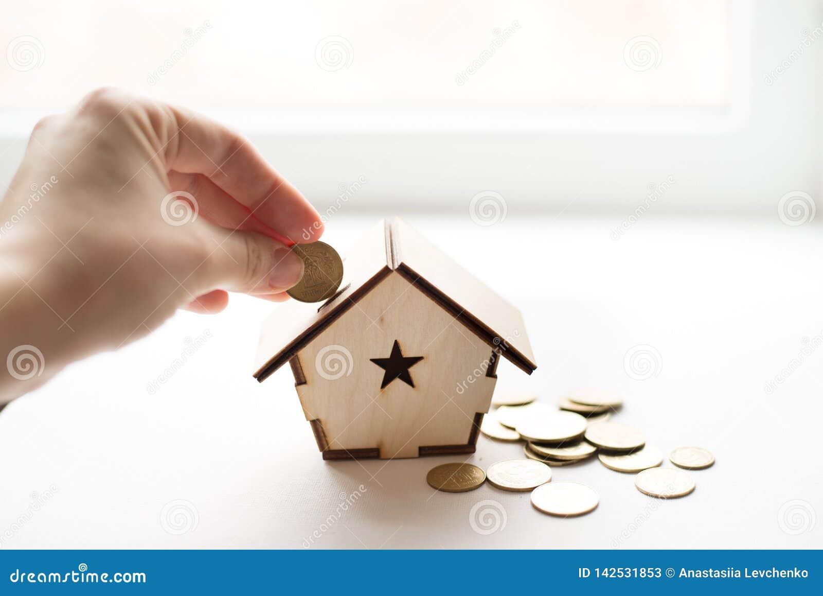 把硬币放的手特写镜头在木屋存钱罐中在白色背景上 安置文本 攒钱,房屋贷款,抵押,a