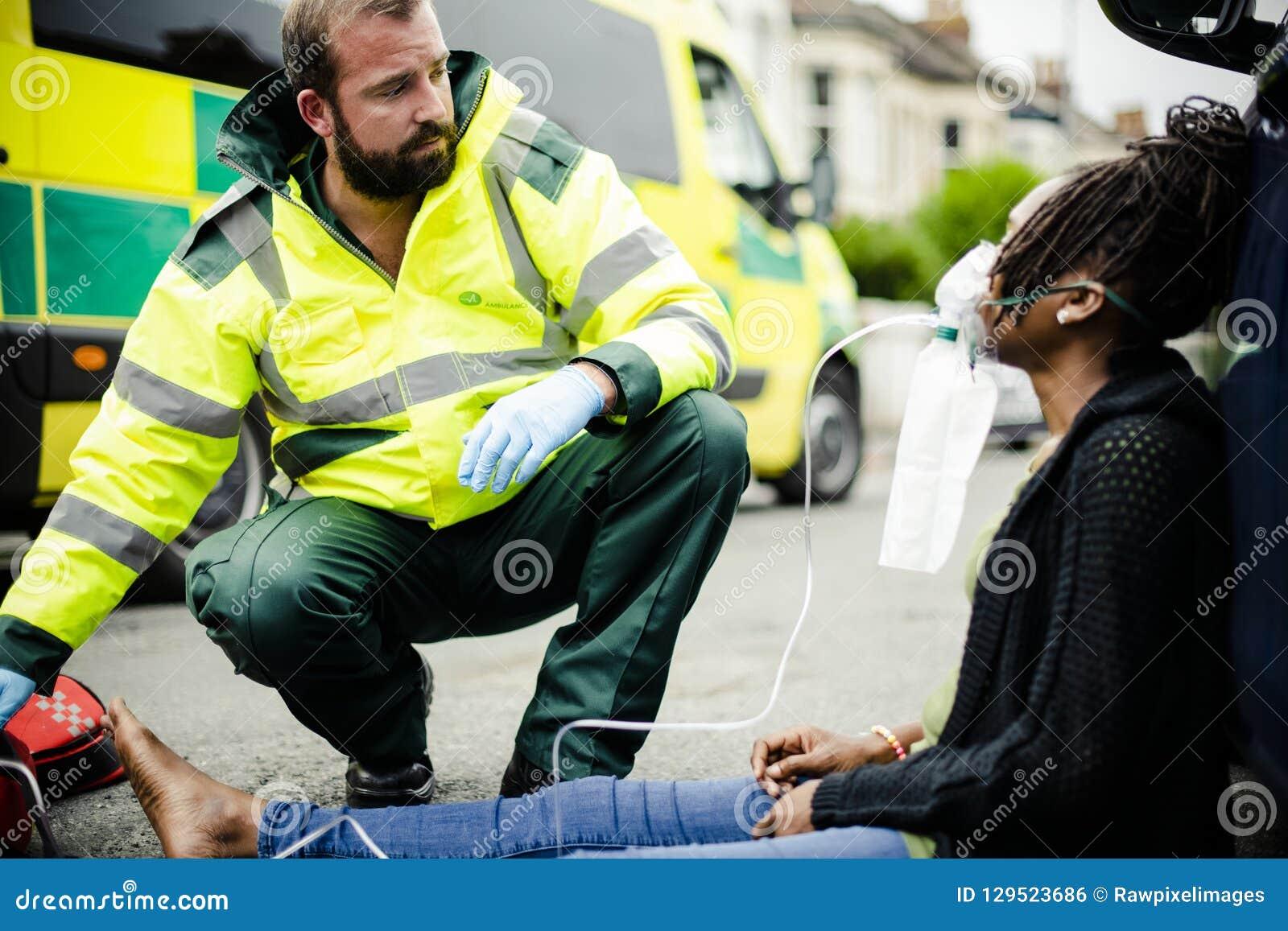 投入在氧气面罩的男性医务人员对路的一名受伤的妇女