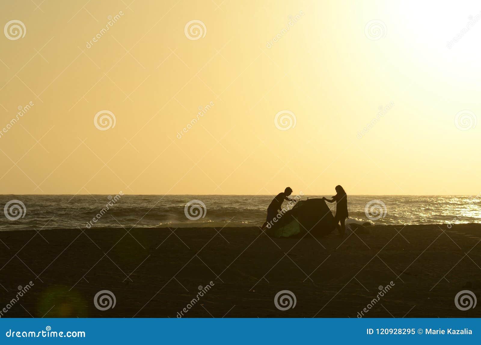 投入帐篷的年轻夫妇男人和妇女剪影在热带海滩