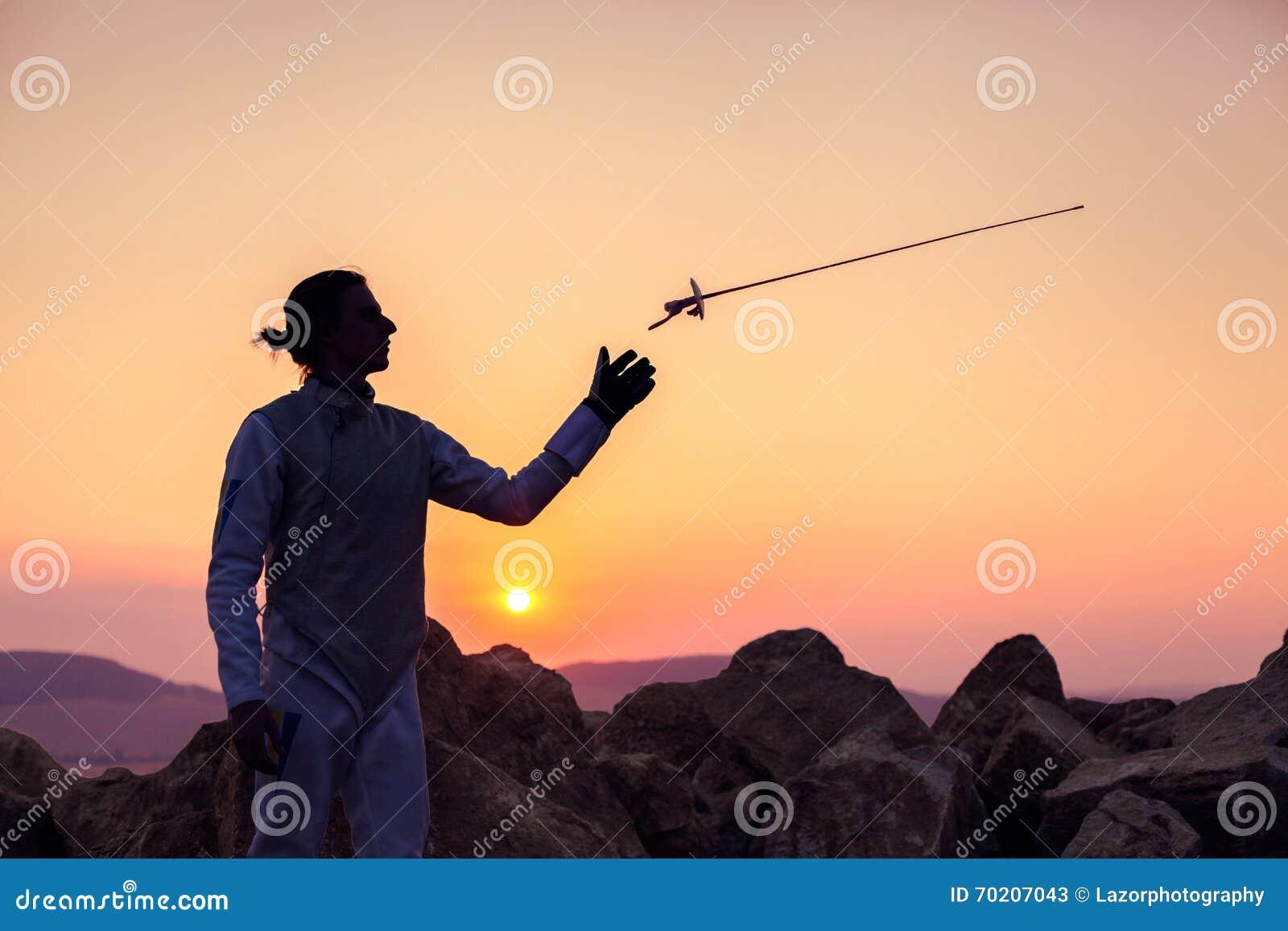 投掷他在日落天空和岩石背景的击剑者人操刀的剑
