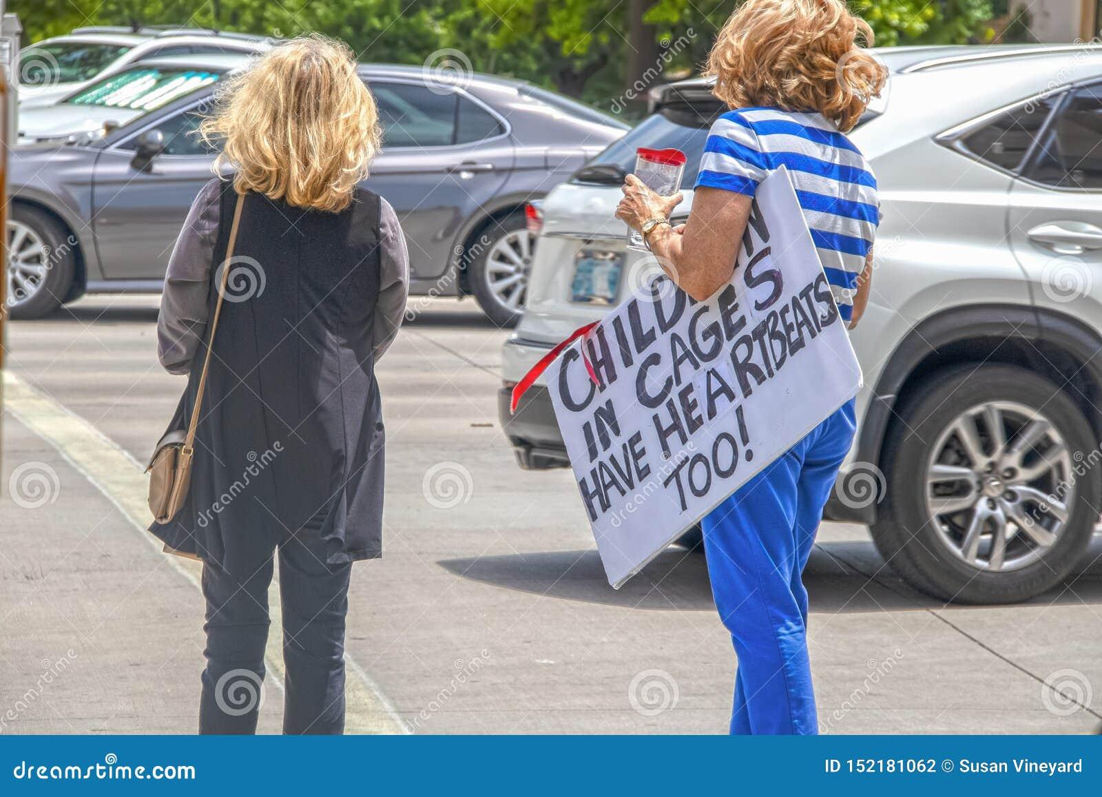 抗议在笼子-移民问题的孩子-两个不可能验明的妇女抗议者穿过拥挤的街-说的一个运载的标志
