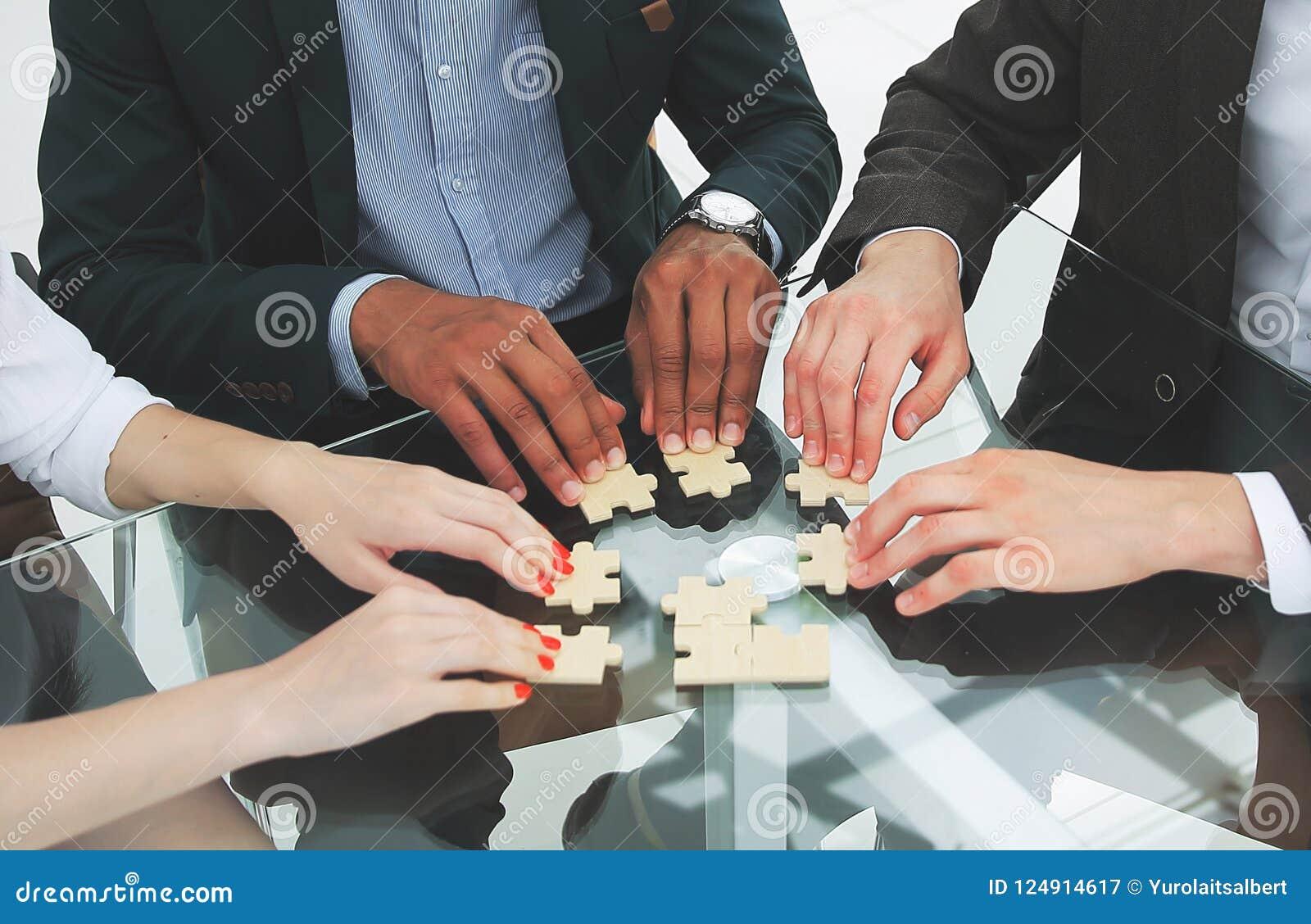 折叠难题的成功的企业队坐在书桌后