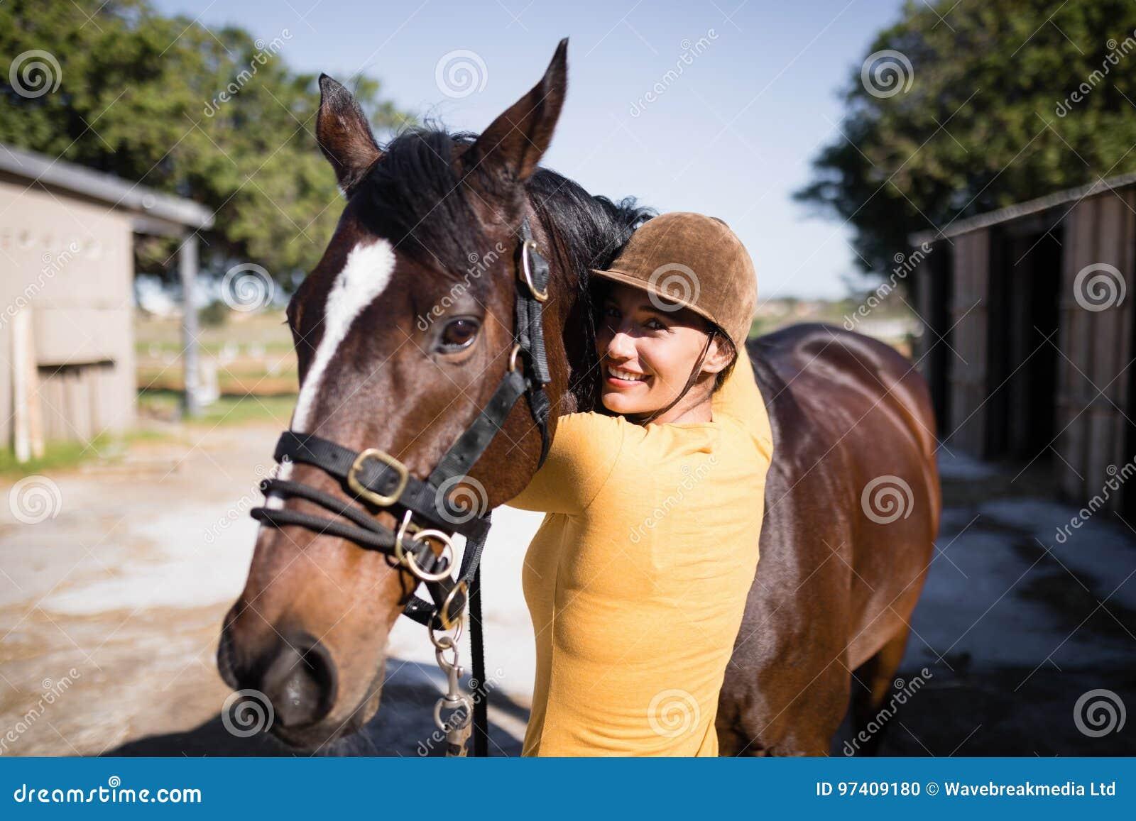 抚摸马的微笑的女性骑师画象