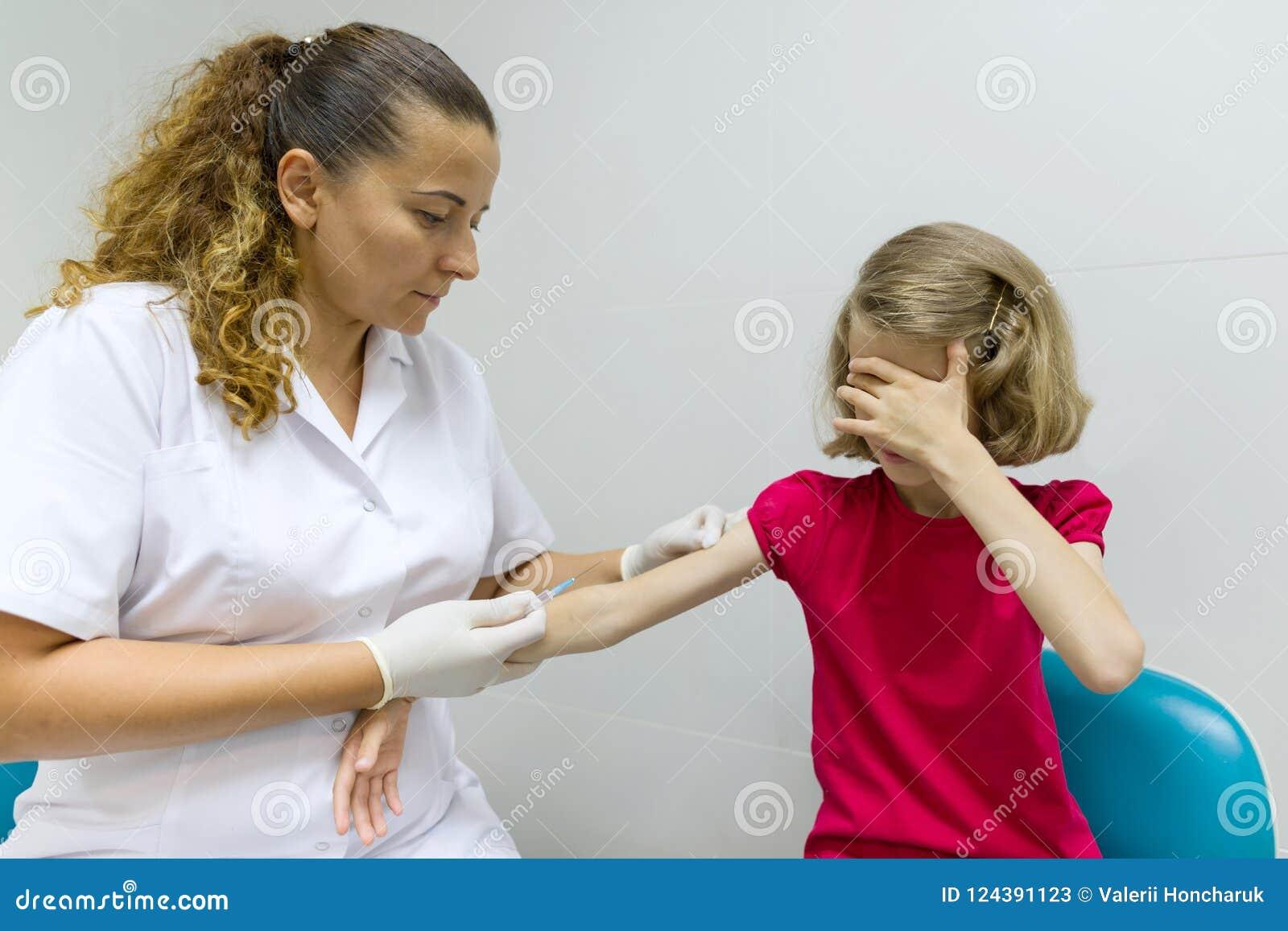 护士使用一个注射器接种儿童女孩 在肩膀的接种,在医院 医学,医疗保健, pediatry和