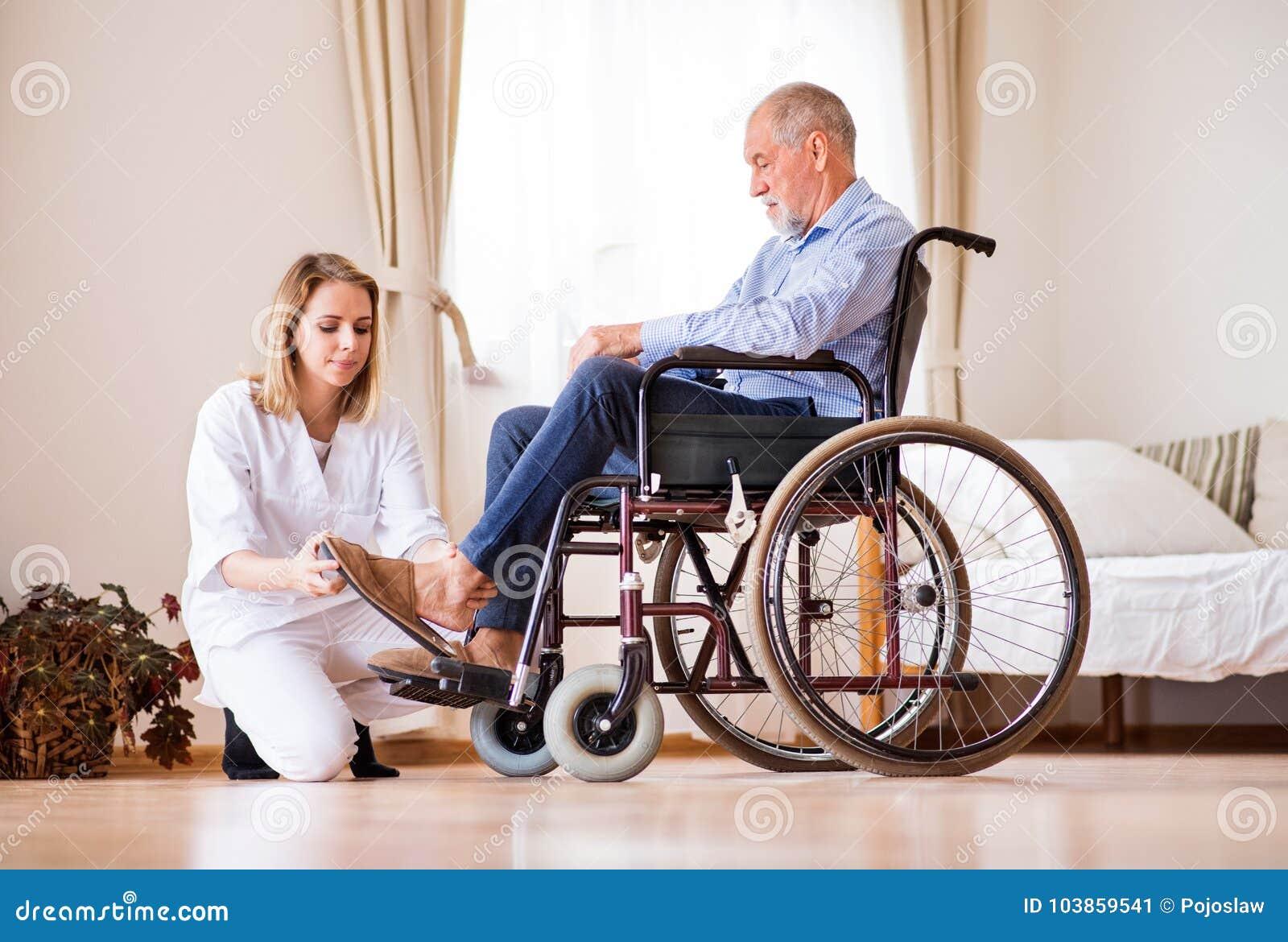 护士和老人轮椅的在家庭参观期间