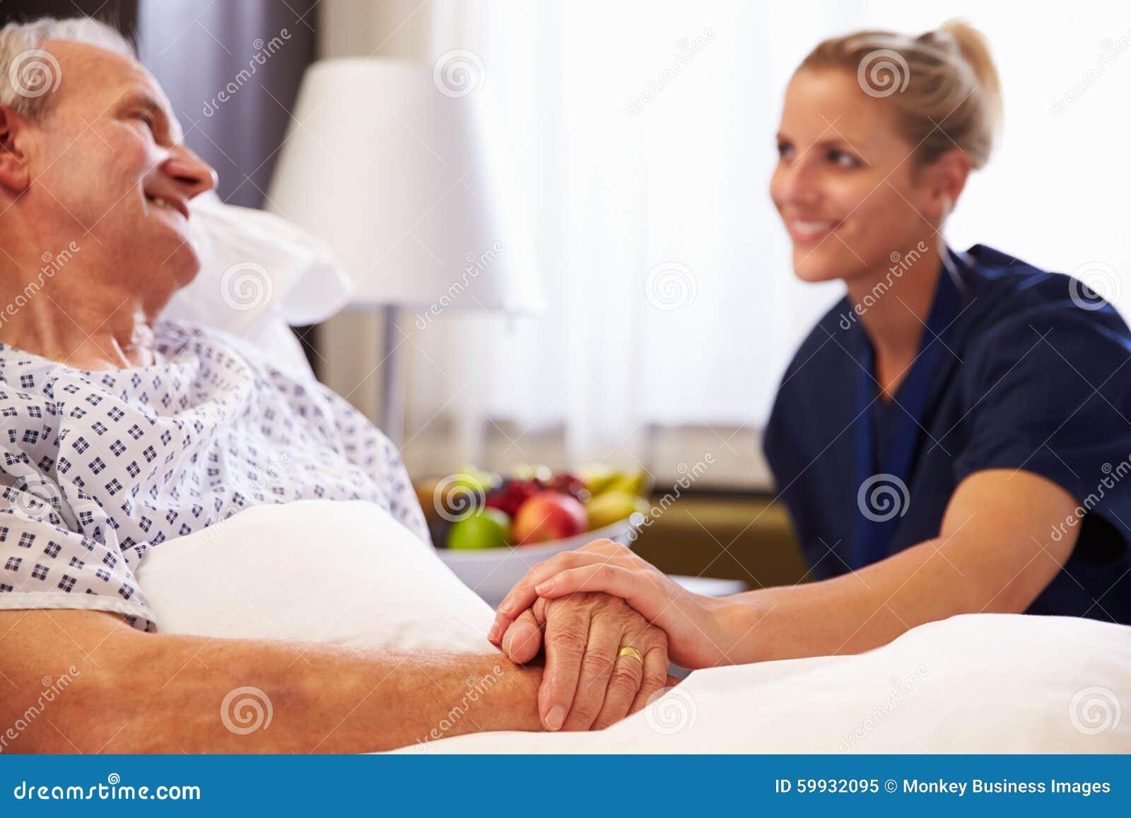护士谈话与资深男性患者在医院病床上