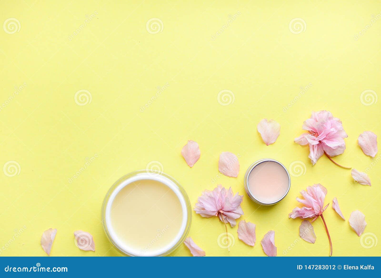 护手霜,在黄色背景的唇膏,花瓣 文本的空间
