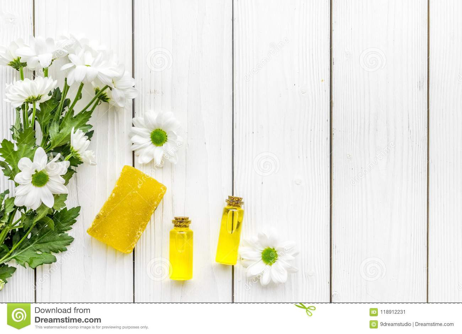 护肤的化妆用品与春黄菊 上油,用肥皂擦洗在白色木背景顶视图拷贝空间