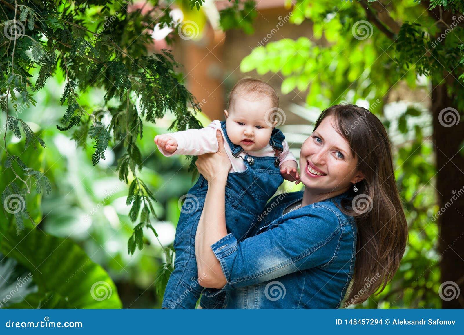 抱着一个婴孩步行的愉快的年轻女人在公园