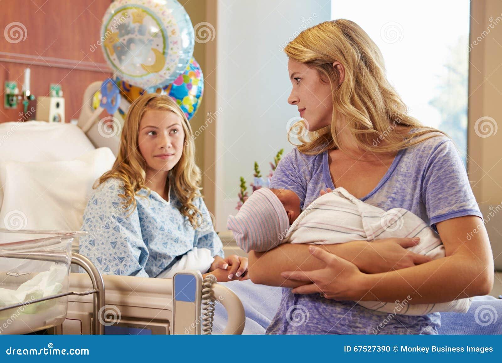 抱着十几岁的女儿的新出生的婴孩的母亲在医院