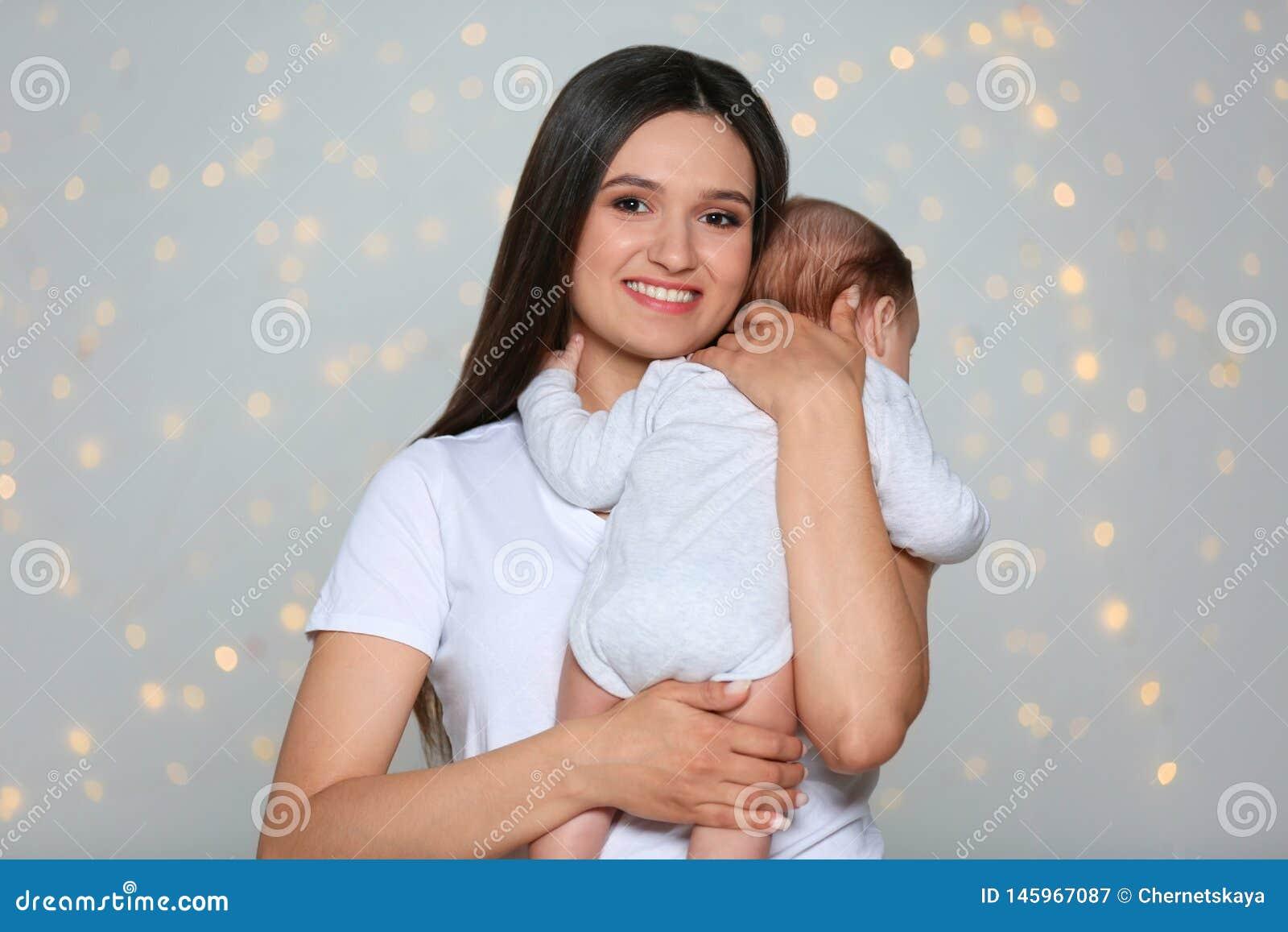 抱着她可爱的婴孩的年轻母亲