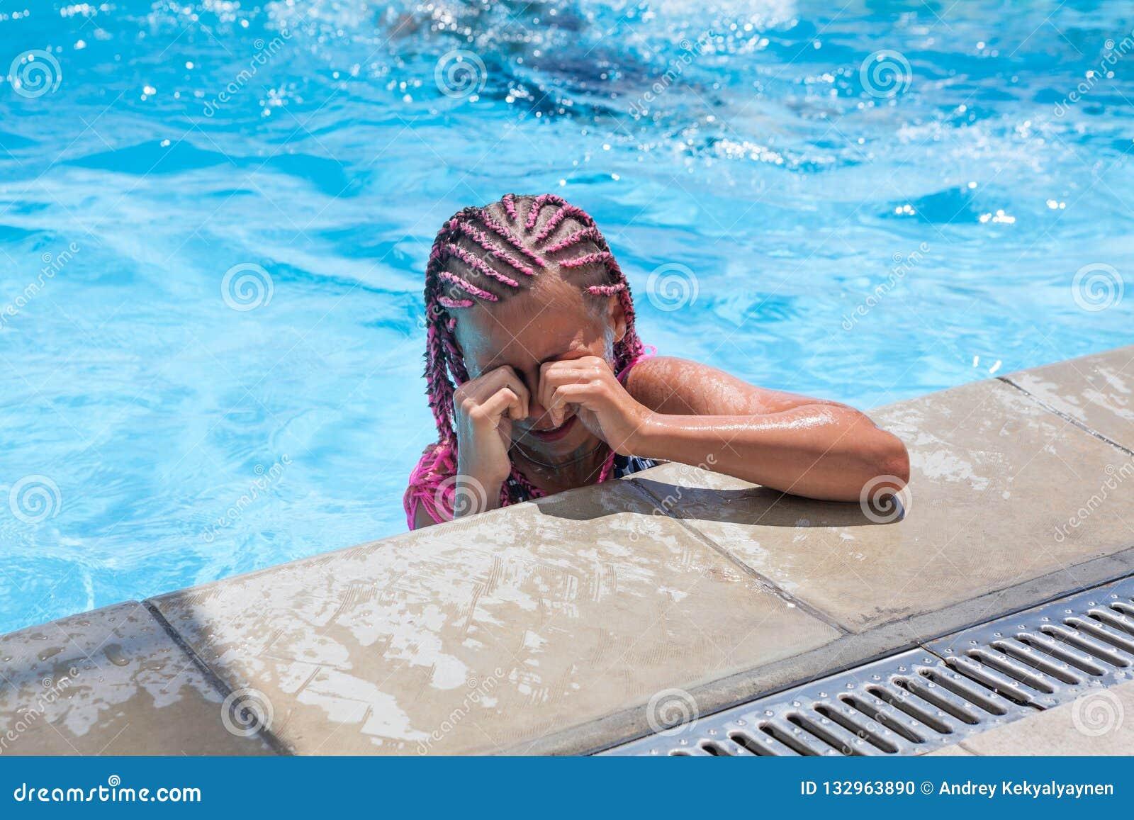 抹从眼睛的青春期前的女孩水,当游泳在水池时