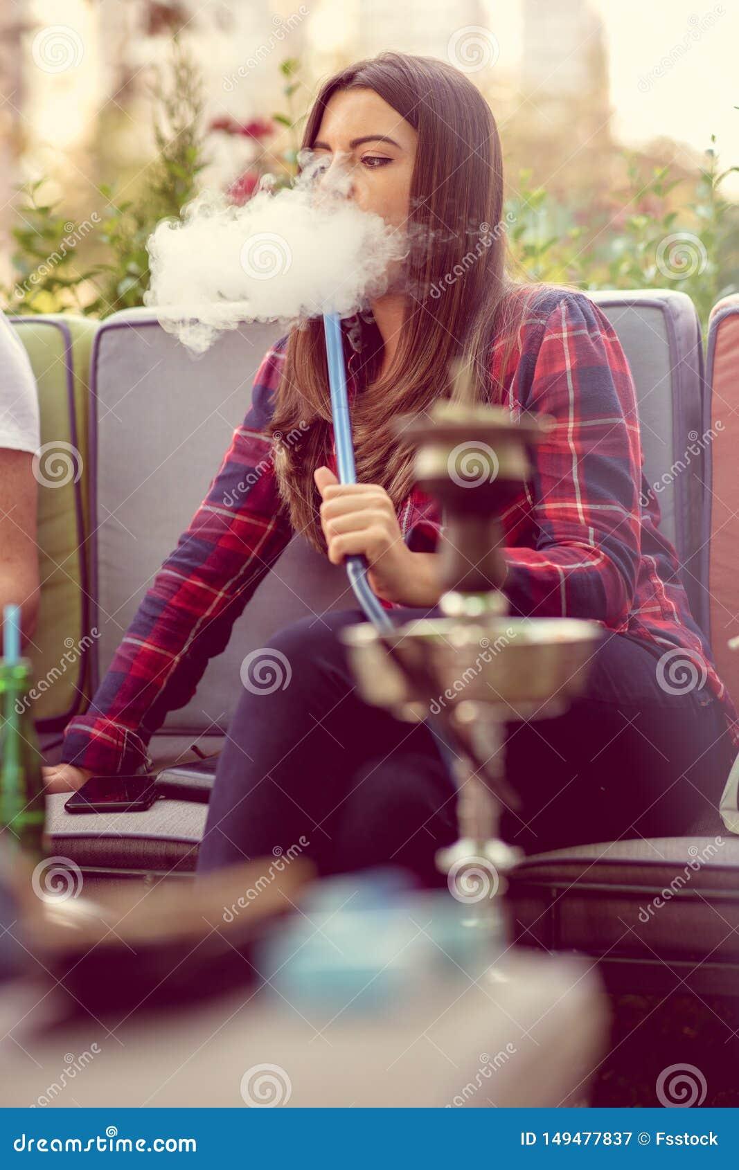 抽水烟筒的年轻女人户外 乐趣抽烟 城市在背景中