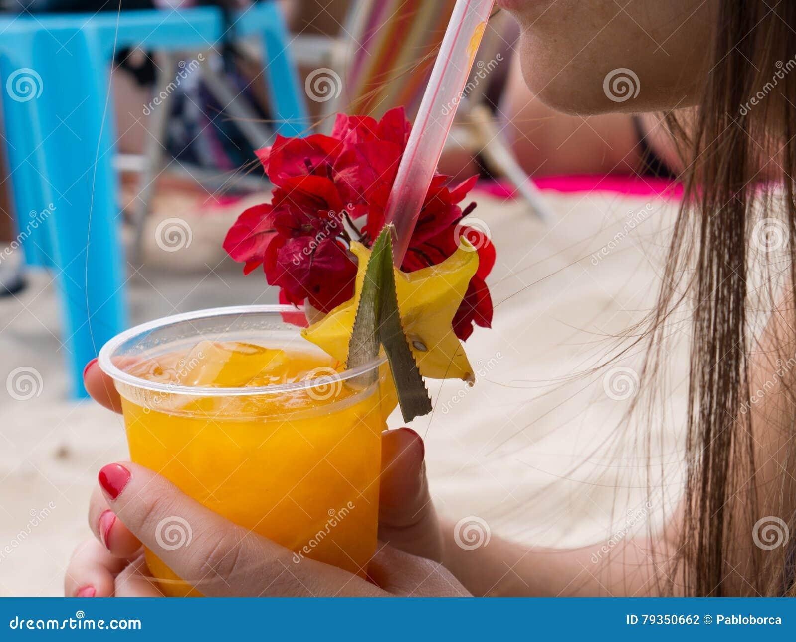 拉丁在海滩的妇女饮用的芒果汁