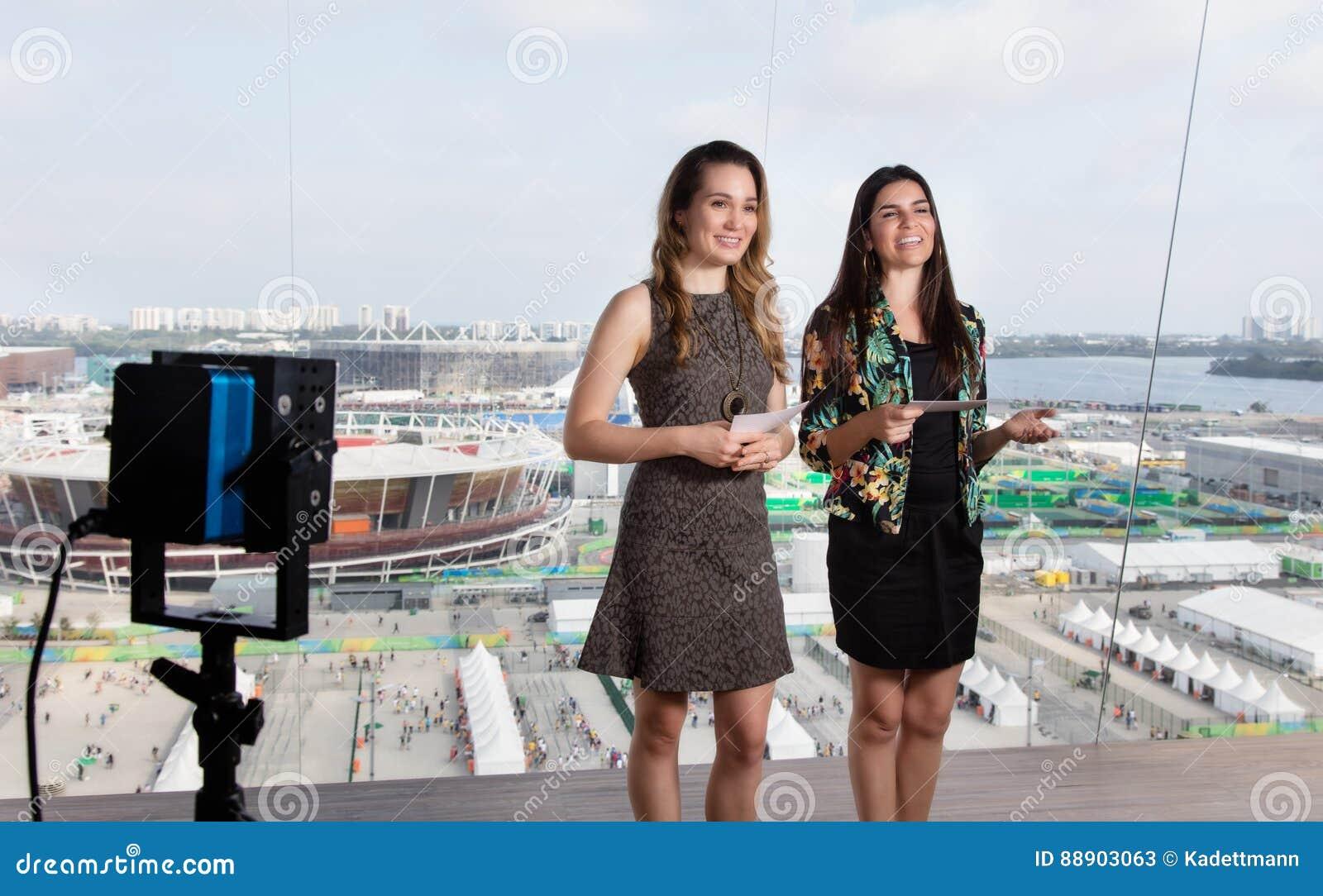 拉丁女性赠送者和白种人妇女电视演播室的