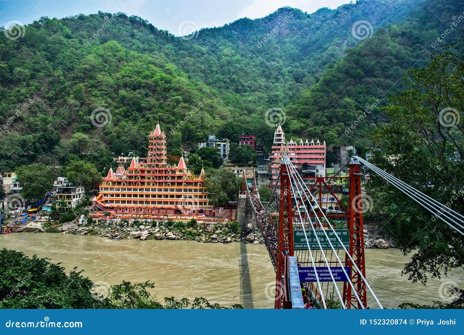 拉克什曼jhula吊桥在有小船的瑞诗凯诗在haridwar ganga的河和漂流