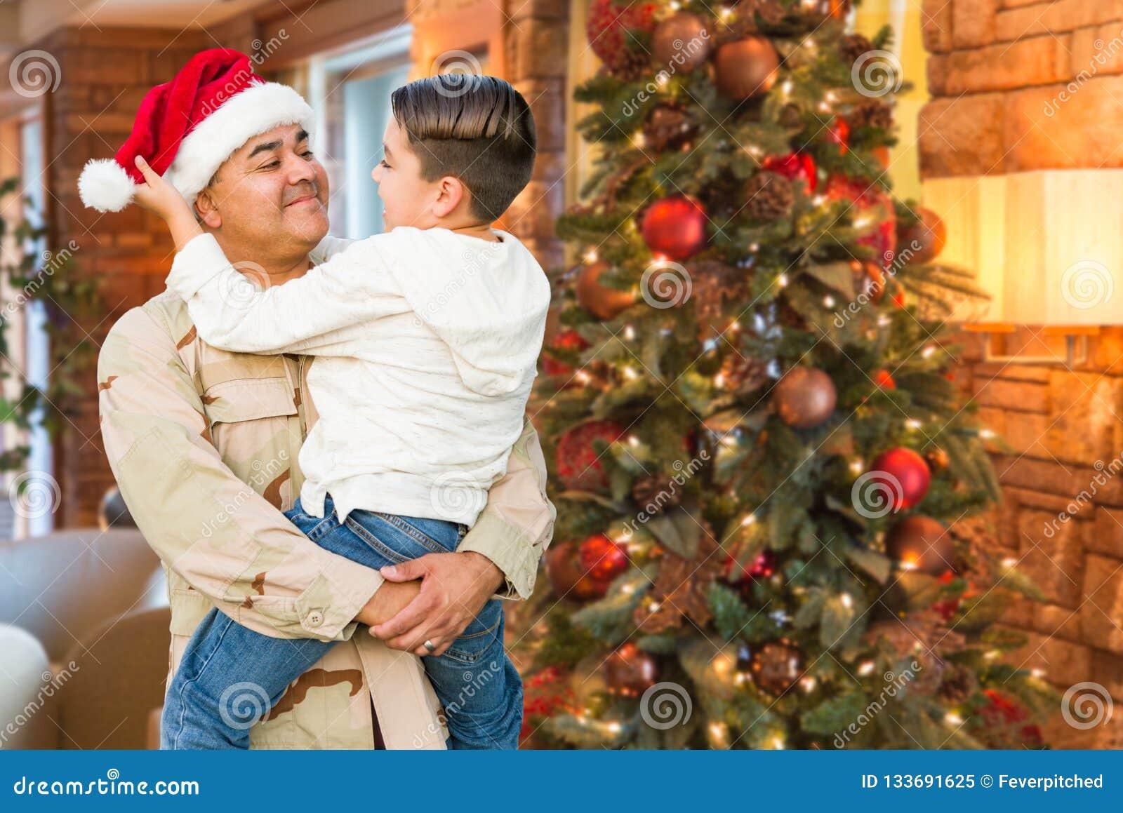 拉美裔戴圣诞老人帽子的武力战士拥抱儿子